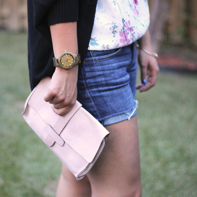 Denim shorts, floral top and a pink clutch