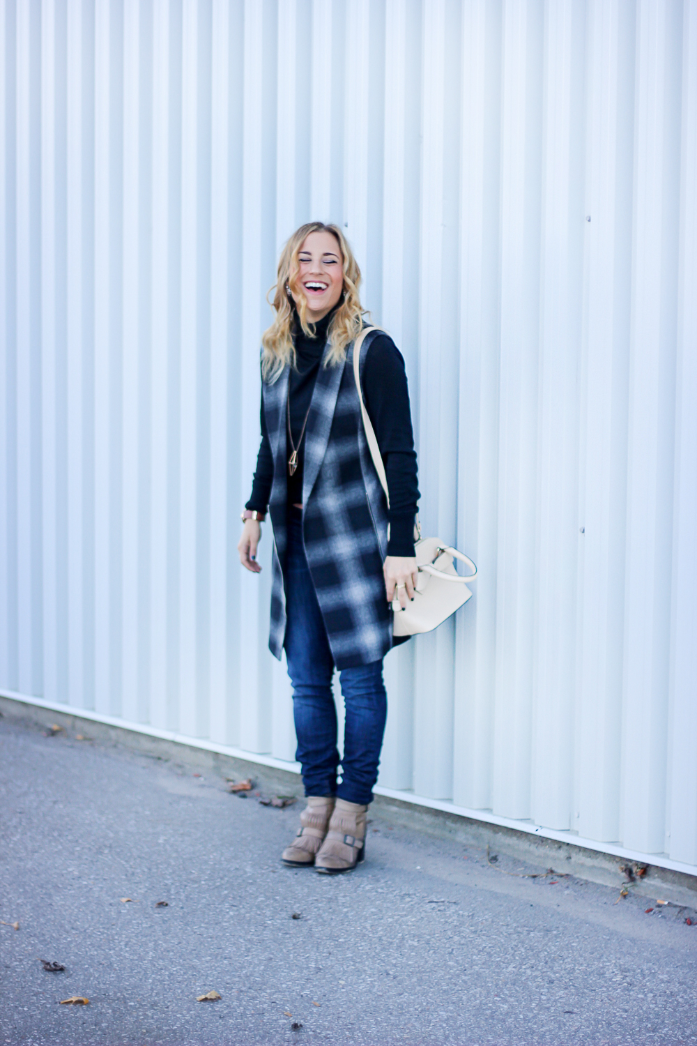 Toronto fashion and lifestyle blogger, Jackie Goldhar, from Something About That, styles a black turtleneck sweater, plaid vest and skinny dark jeans