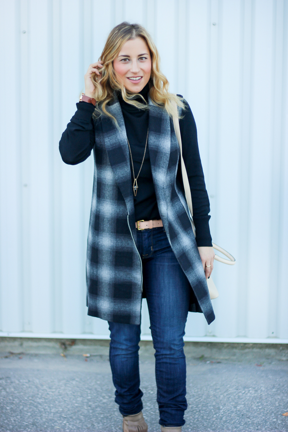Canadian fashion blogger wears a black turtleneck from Gap, a plaid WAYF vest and Hudson skinny jeans