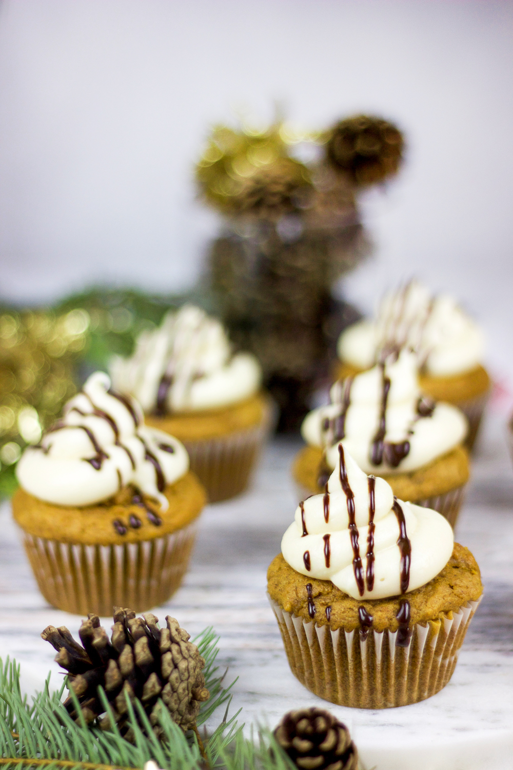 Pumpkin spice cupcakes with a chocolate ganache filling, topped with cream cheese frosting