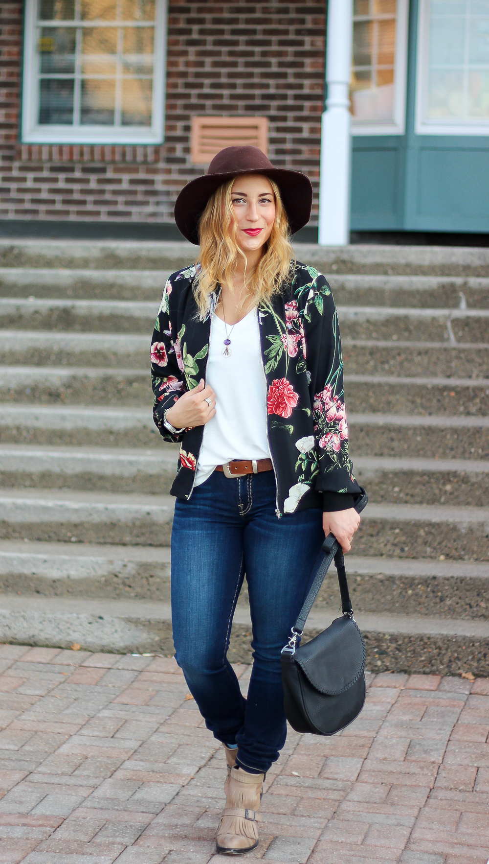 Canadian fashion and lifestyle blogger, Jackie Goldhar from Something About That, wearing a floral bomber jacket and Guess jeans from Jean Machine