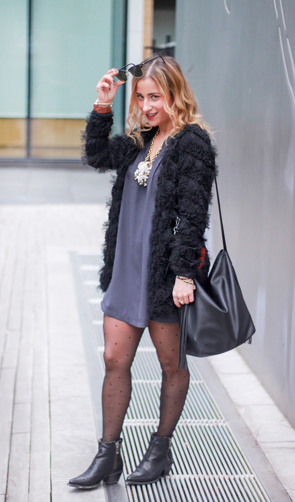Canadian fashion and lifestyle blogger, Jackie Goldhar, wears a black furry jacket and a Pink Martini dress to a holiday brunch party