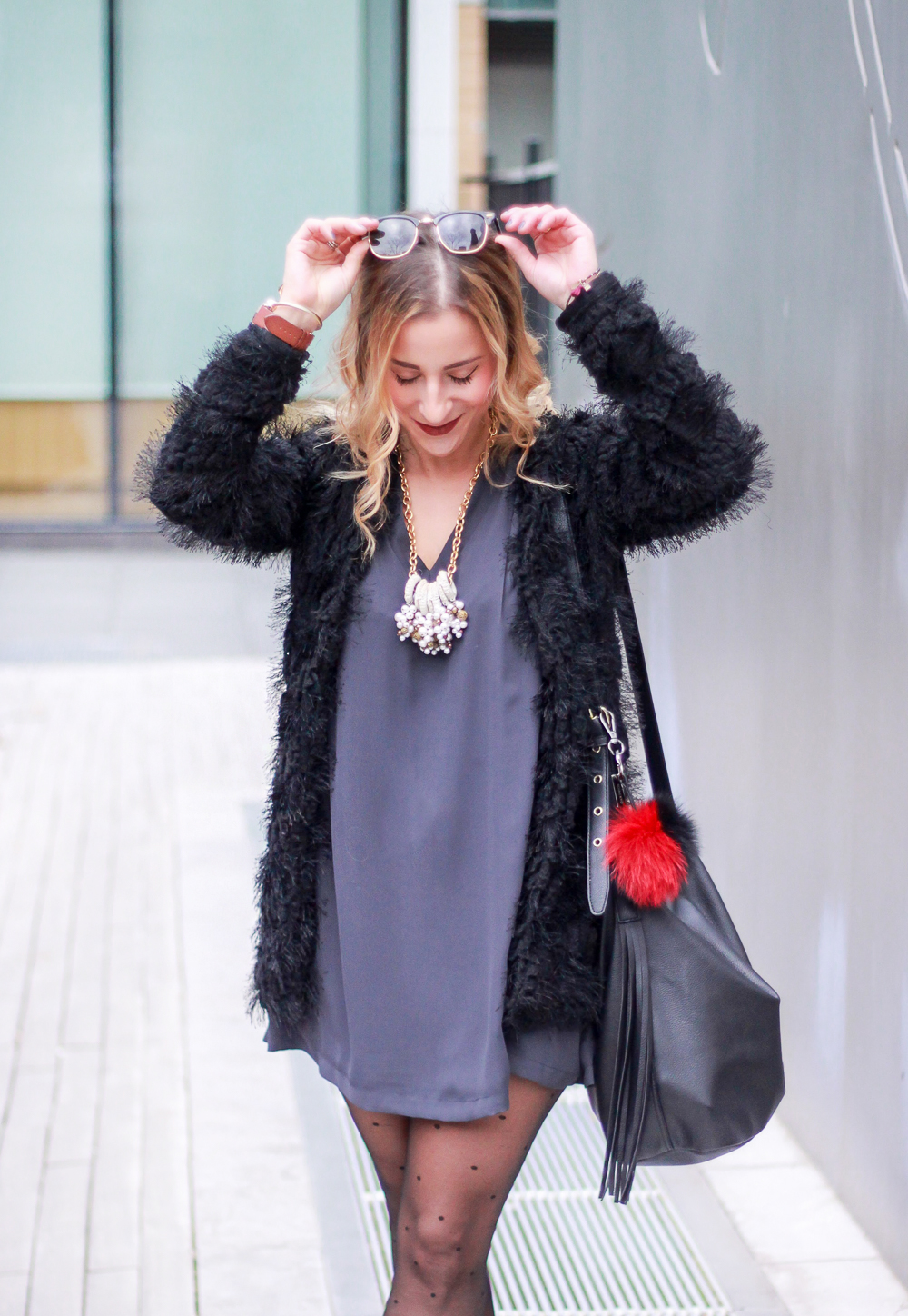 Toronto fashion and lifestyle blogger, Jackie Goldhar, wearing a furry black coat, simple dress and a gold statement necklace to a holiday brunch
