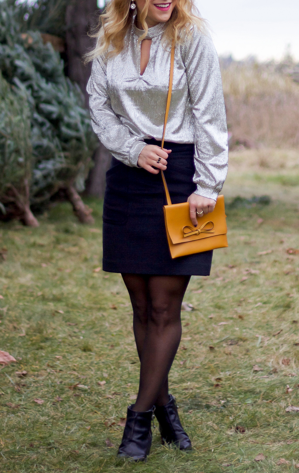 Holiday outfit idea, wearing a metallic top and a fitted skirt with black tights