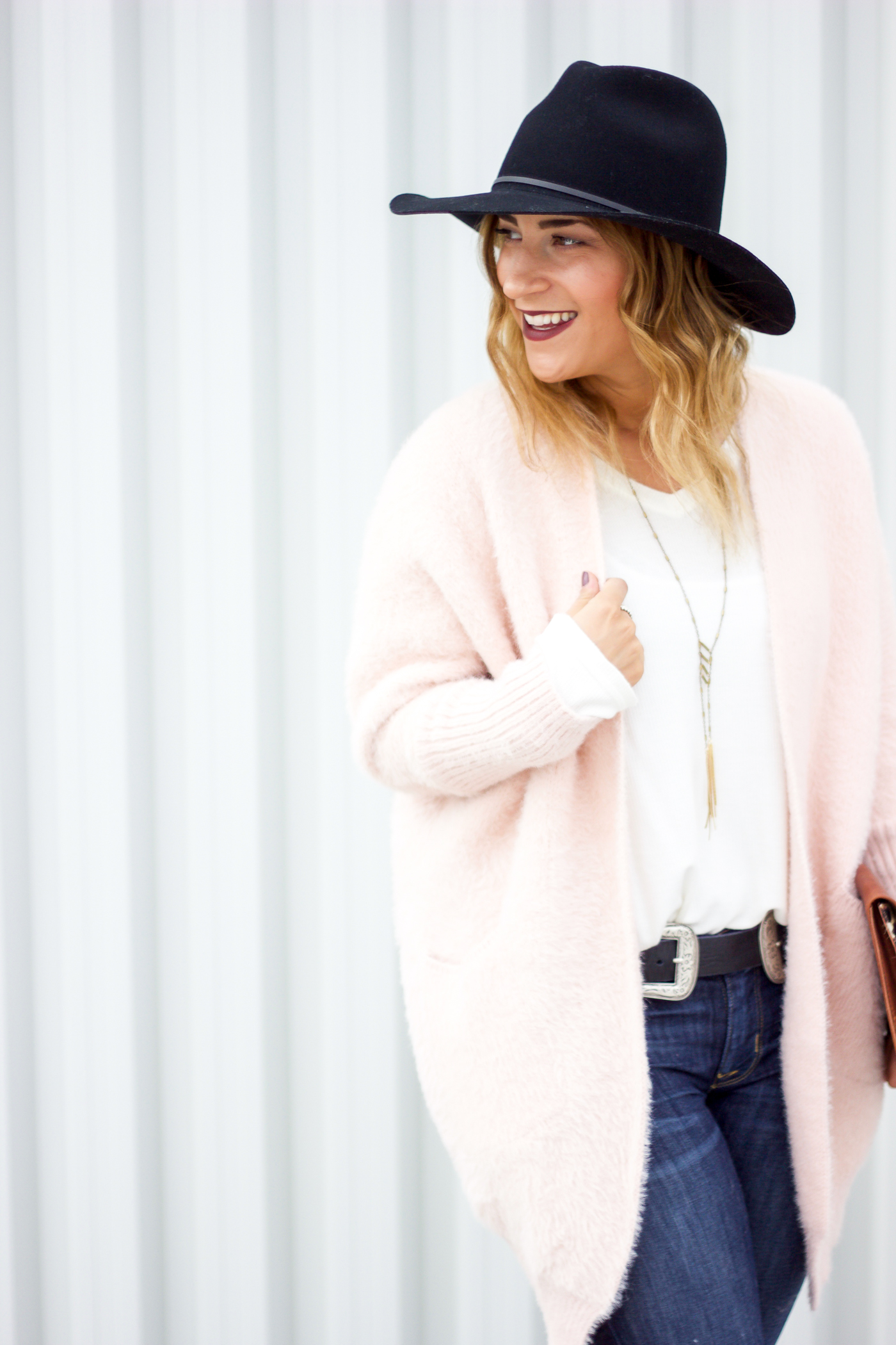 Canadian Fashion and lifestyle blogger, Jackie Goldhar is wearing a pink cardigan from Chicwish and accessories from BRAVE Leather