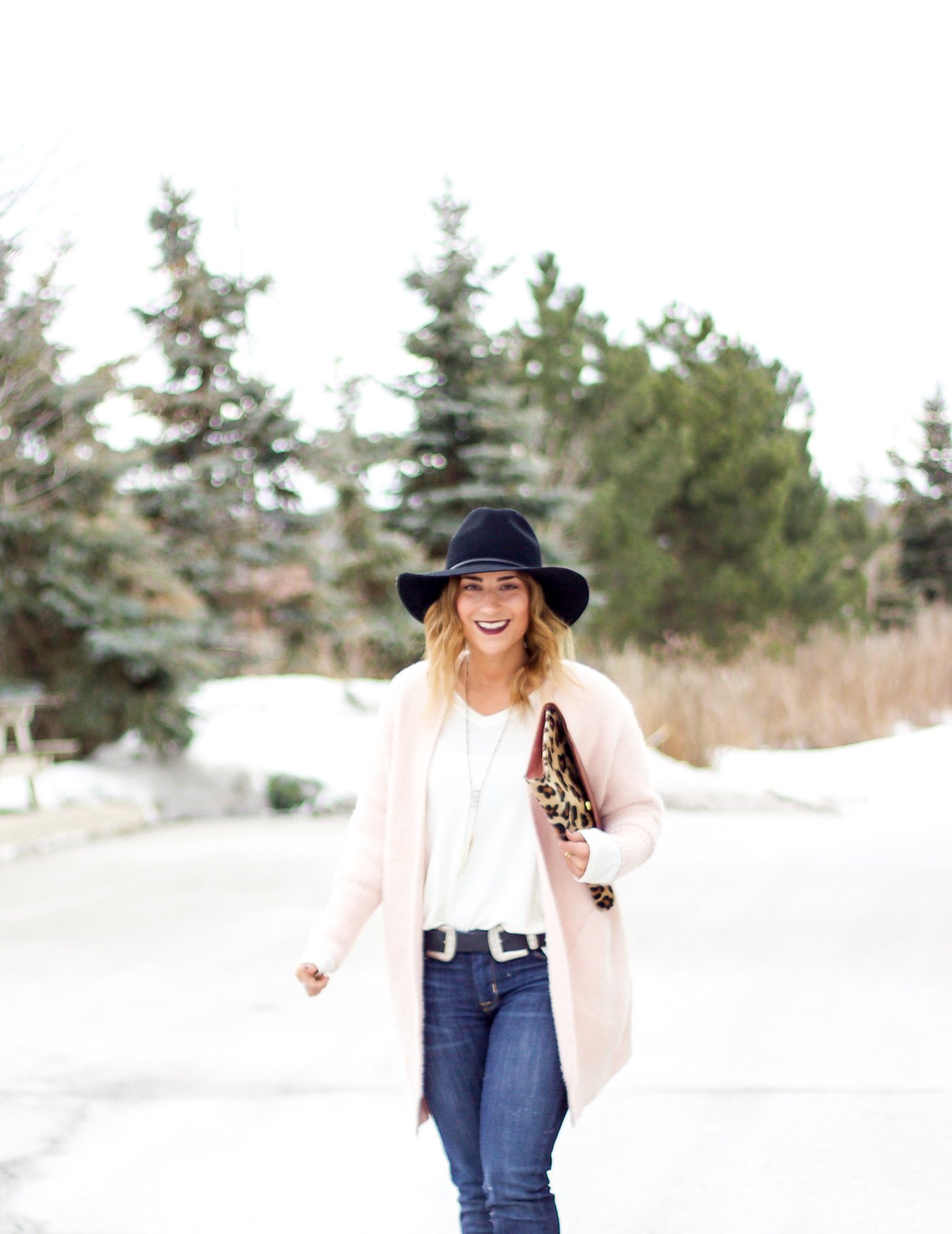 Toronto fashion and lifestyle blogger, Jackie of Something About That is wearing a fuzzy pink cardigan from Chicwish, a hat from Aritzia, BRAVE Leather belt and Hudson skinny jeans