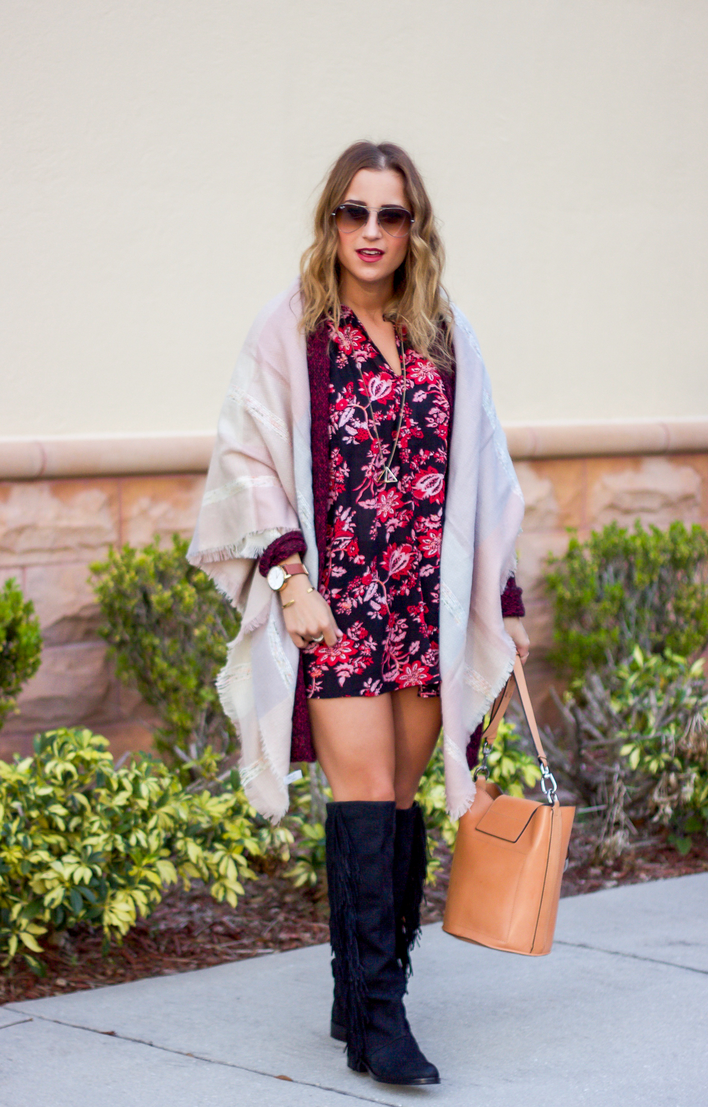 Canadian fashion and lifestyle blogger, wearing a dark floral dress with an oversized blanket scarf and fringe boots