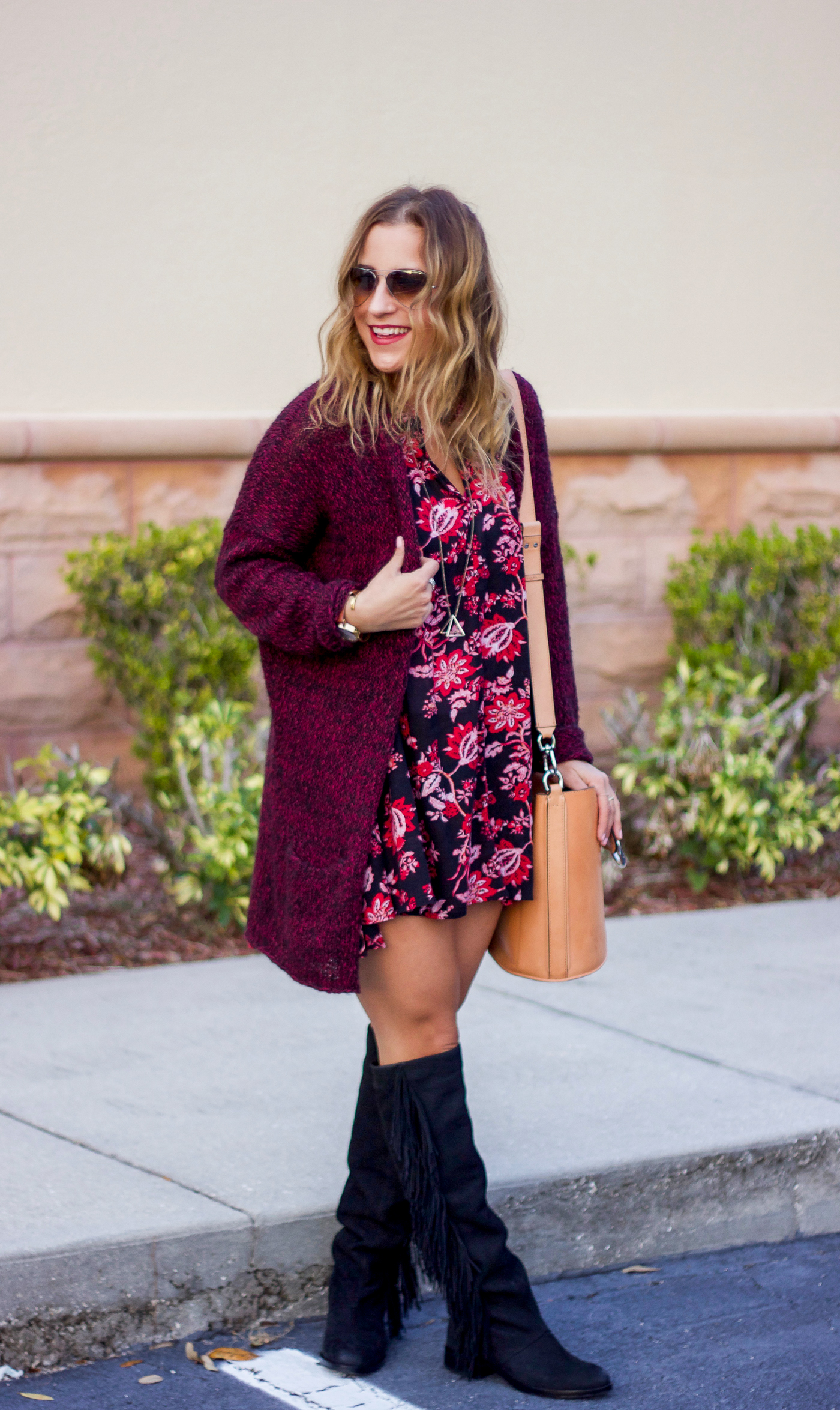 Burgundy cardigan from Aritzia, paired with a dark floral dress from Nordstrom Rack and fringe boots by Sam Edelman