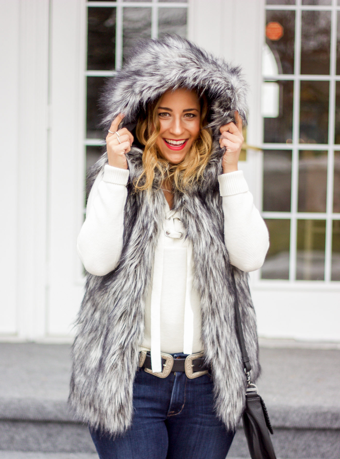 Jackie Goldhar is a top Canadian fashion and lifestyle blogger and she's wearing a faux fur vest with a hood from aritzia