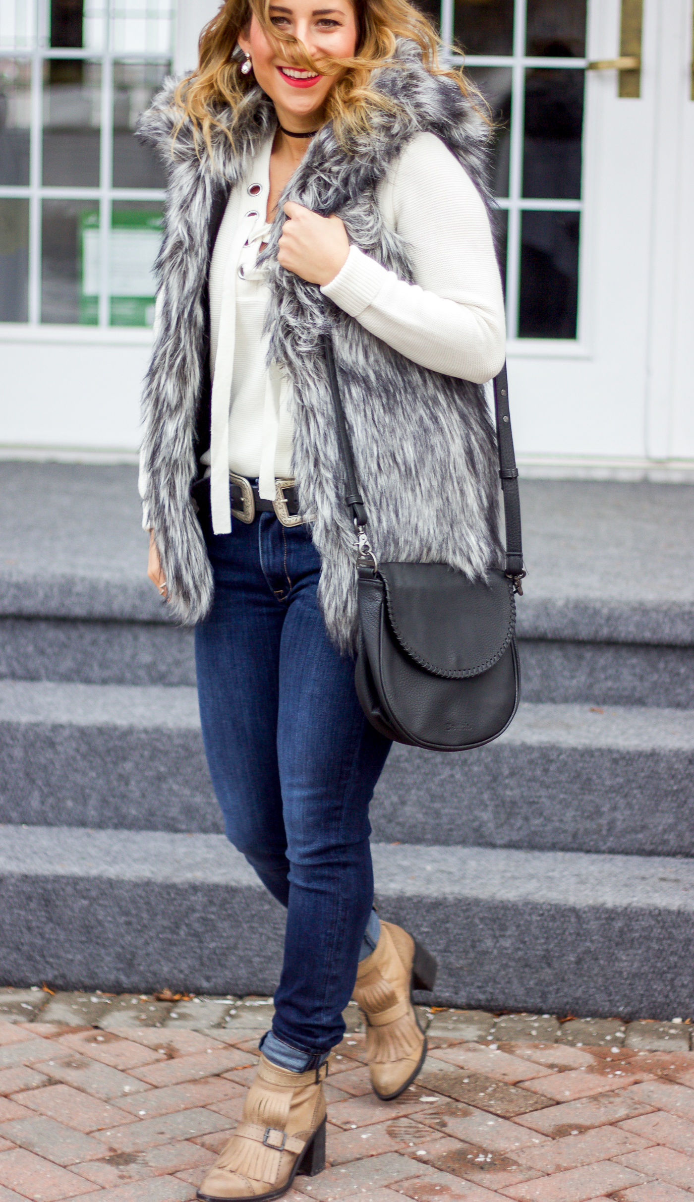 Canadian fashion and lifestyle blogger, Jackie Goldhar of Something About That, is wearing Fidelity jeans, a faux fur vest from Aritzia and a Bench Leather bag