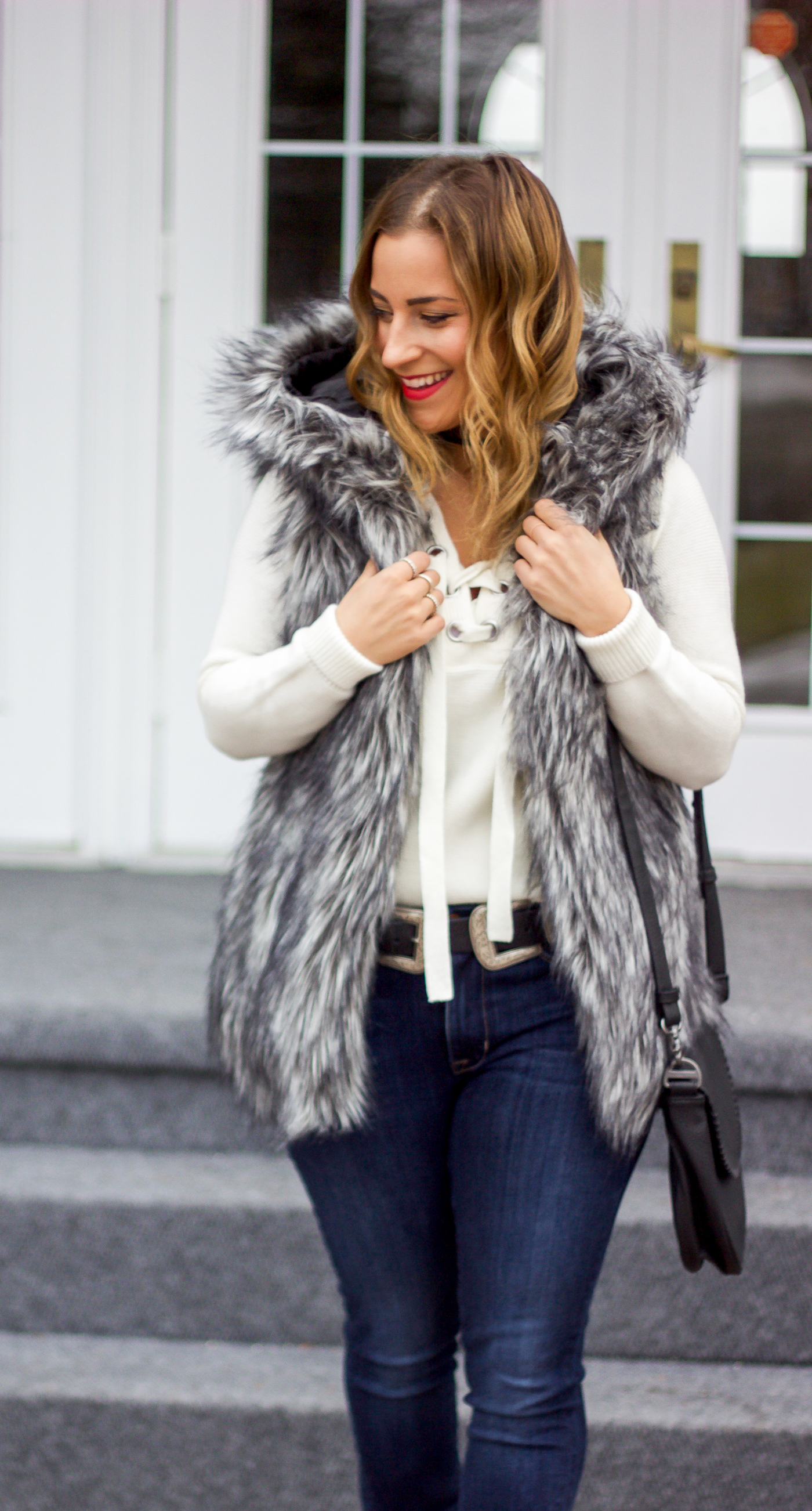 Toronto fashion and lifestyle blogger, Jackie of Something About That is wearing a faux fur vest with a hood from Aritzia and Fidelity jeans