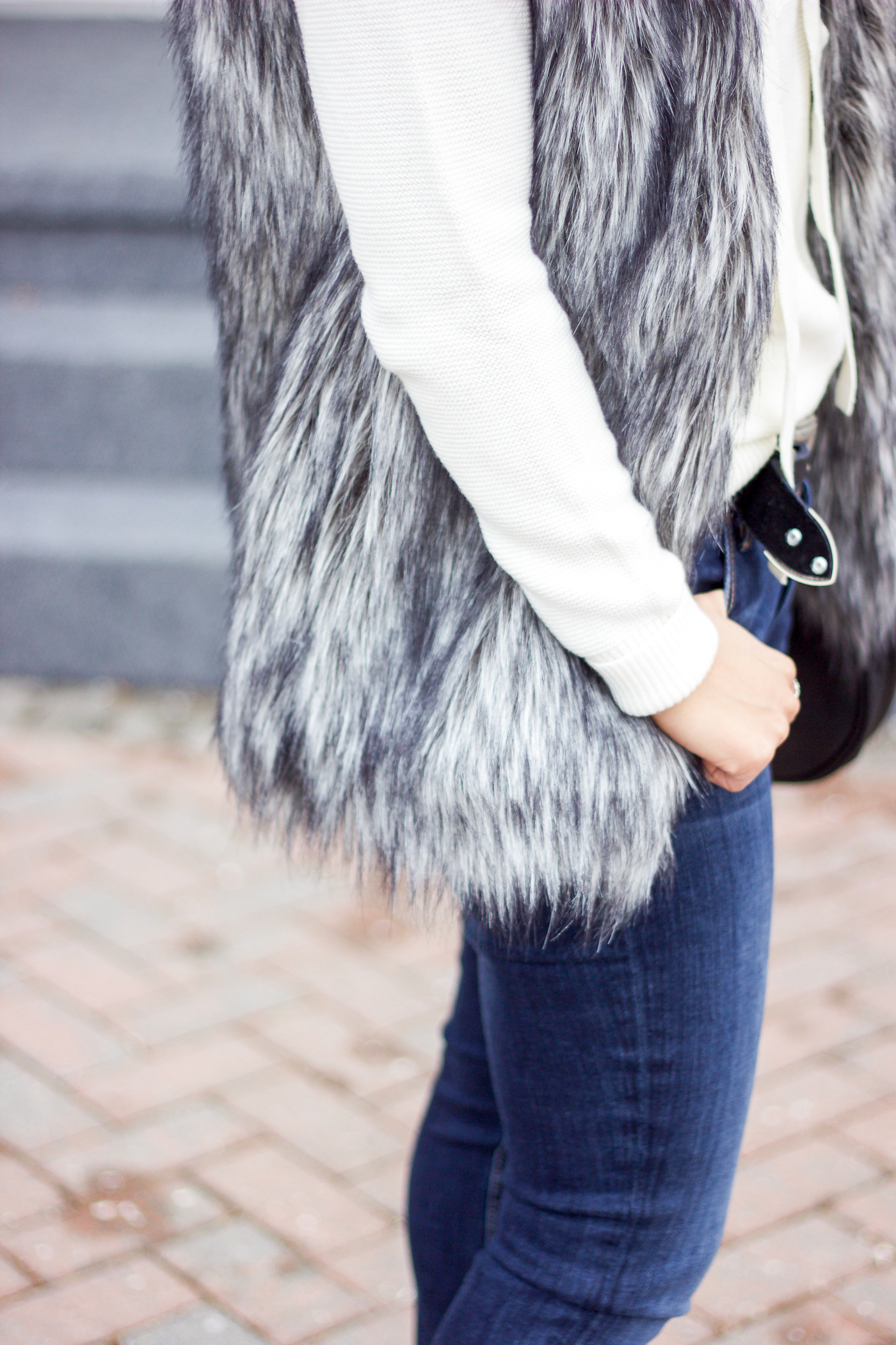 Simple winter outfit idea to wear a faux fur vest with jeans