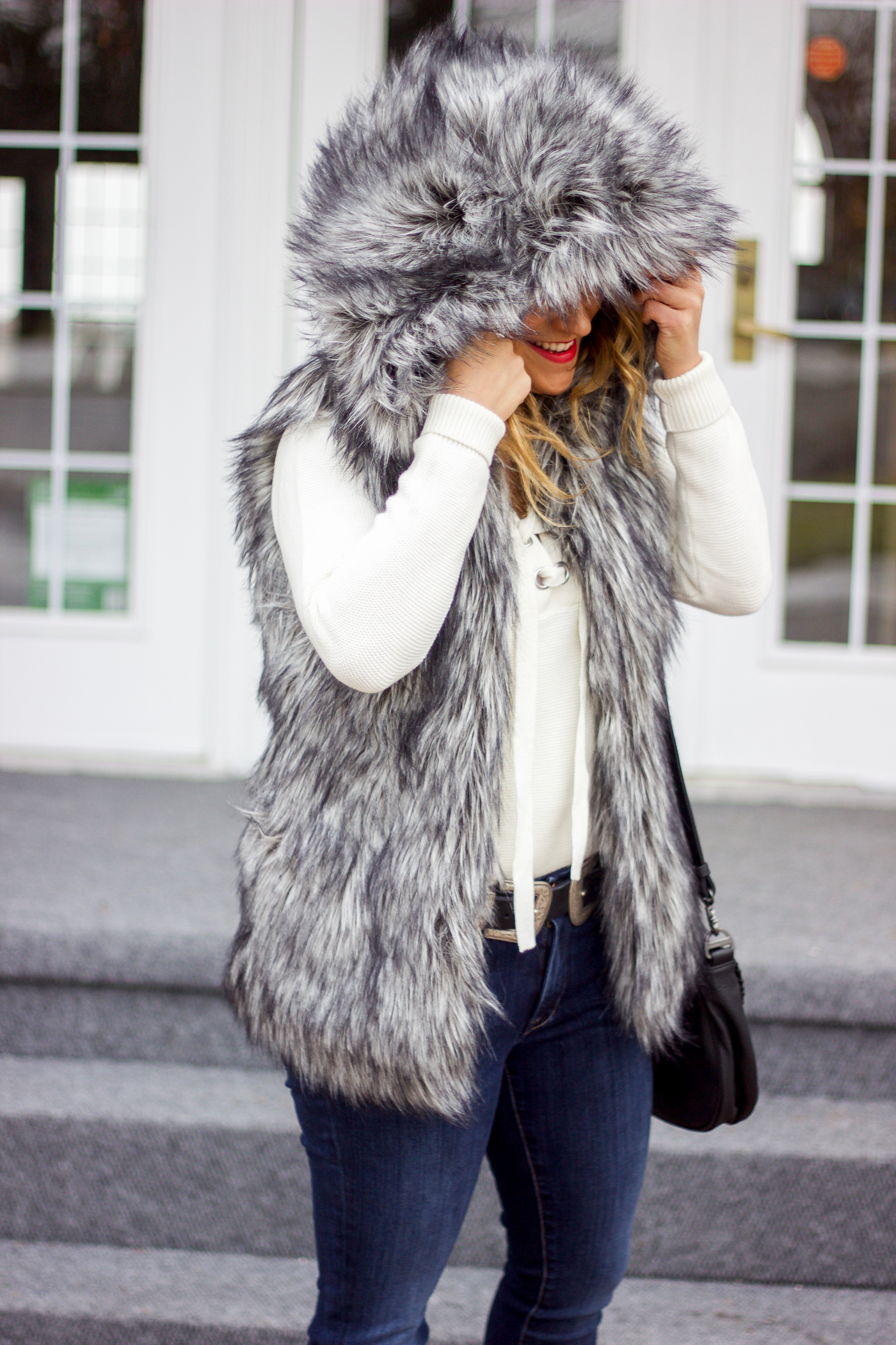 How to stay warm in the winter, wearing a hooded faux fur vest from Aritzia