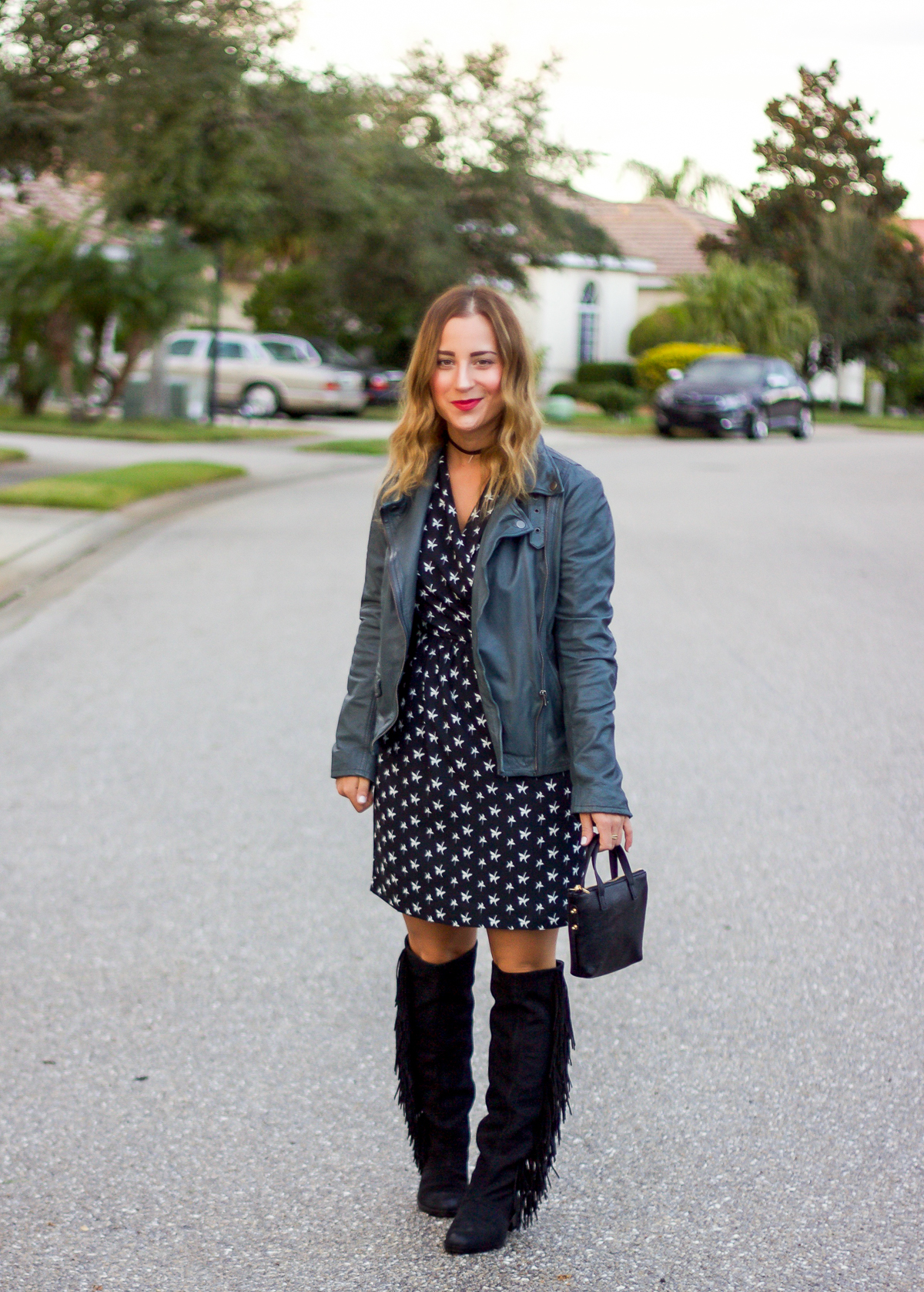 Canadian blogger, Jackie Goldhar of Something About That is wearing a leather moto jacket, black and white printed dress and black Sam Edelman fringe boots