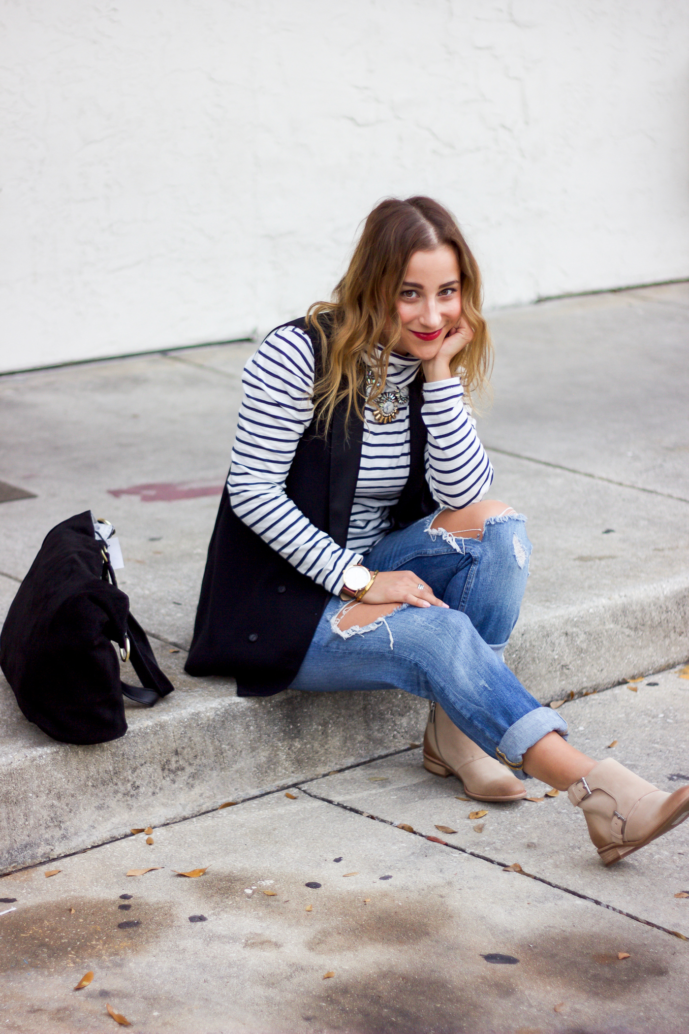 Toronto fashion and lifestyle blogger is wearing an outfit that features a Topshop black vest, striped turtleneck from Madewell and Michael Kors booties from Shopbop