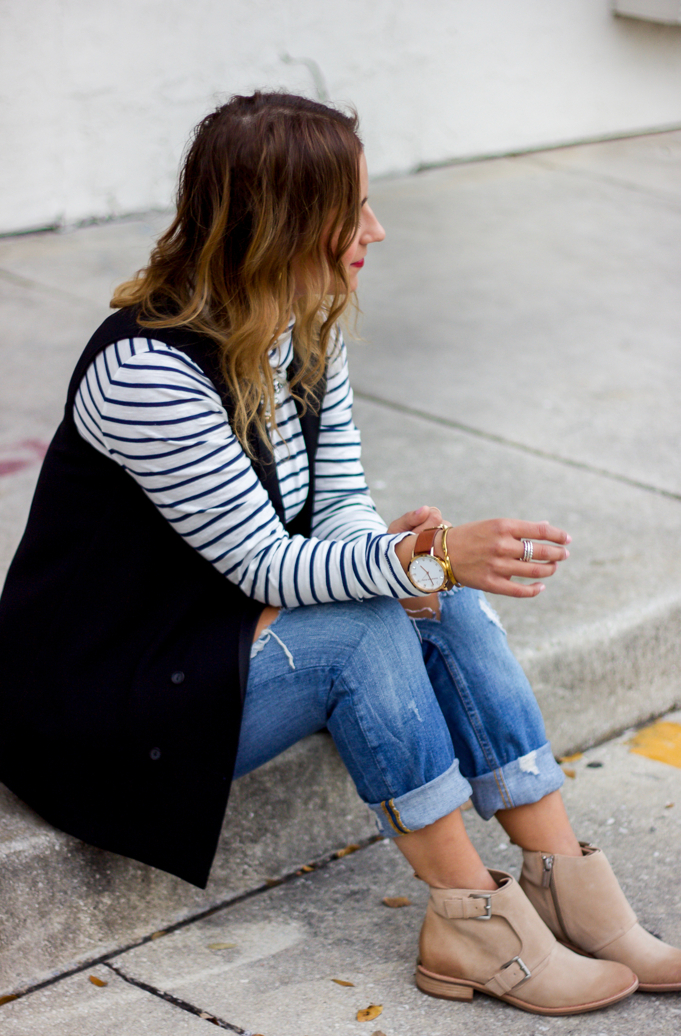Canadian fashion and lifestyle blogger, Jackie of Something About That is wearing a striped turtleneck and a black vest with jeans