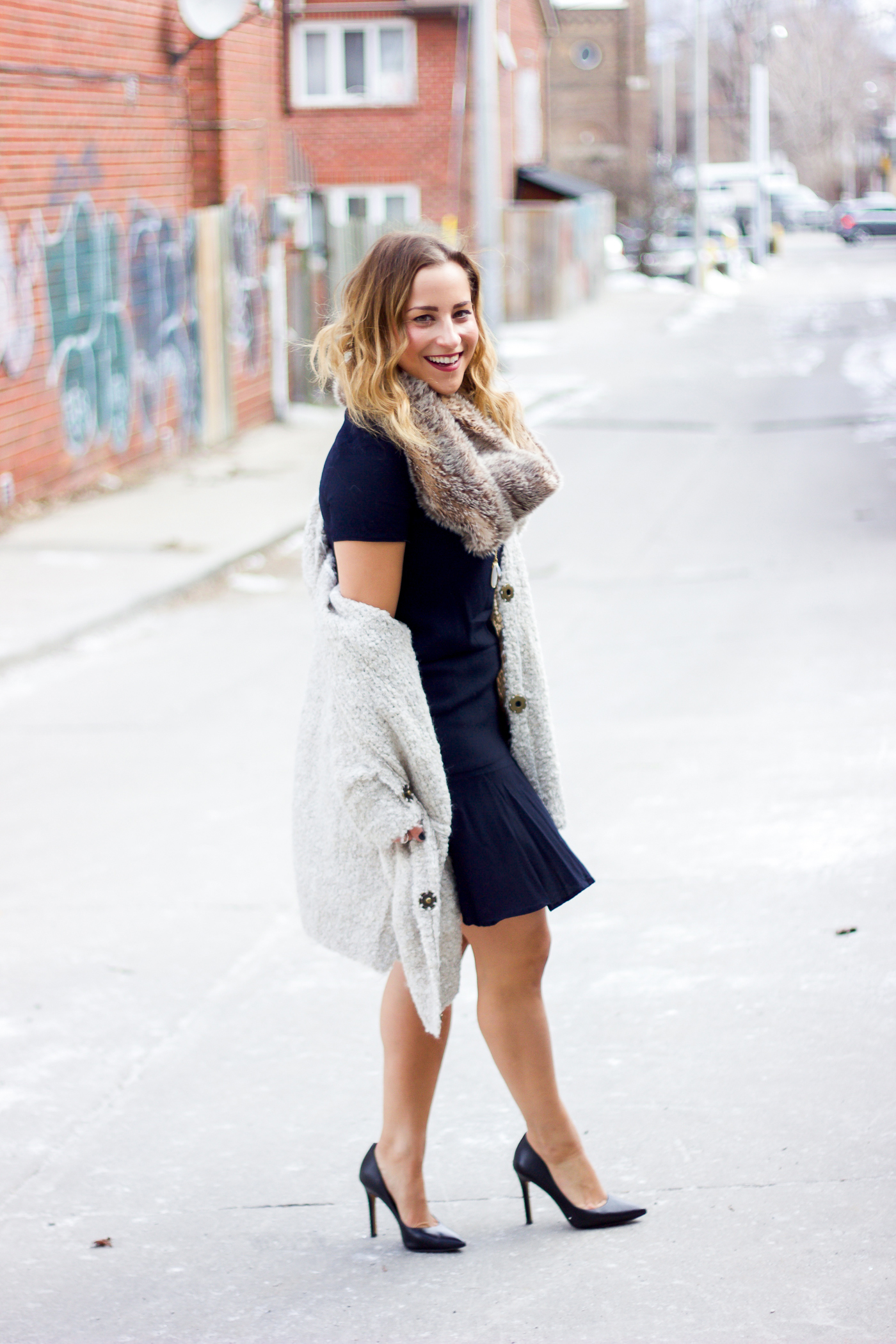 Canadian fashion blogger, Jackie Goldhar from Something About That, is wearing a black dress from Gap with a Free People cardigan and faux fur scarf