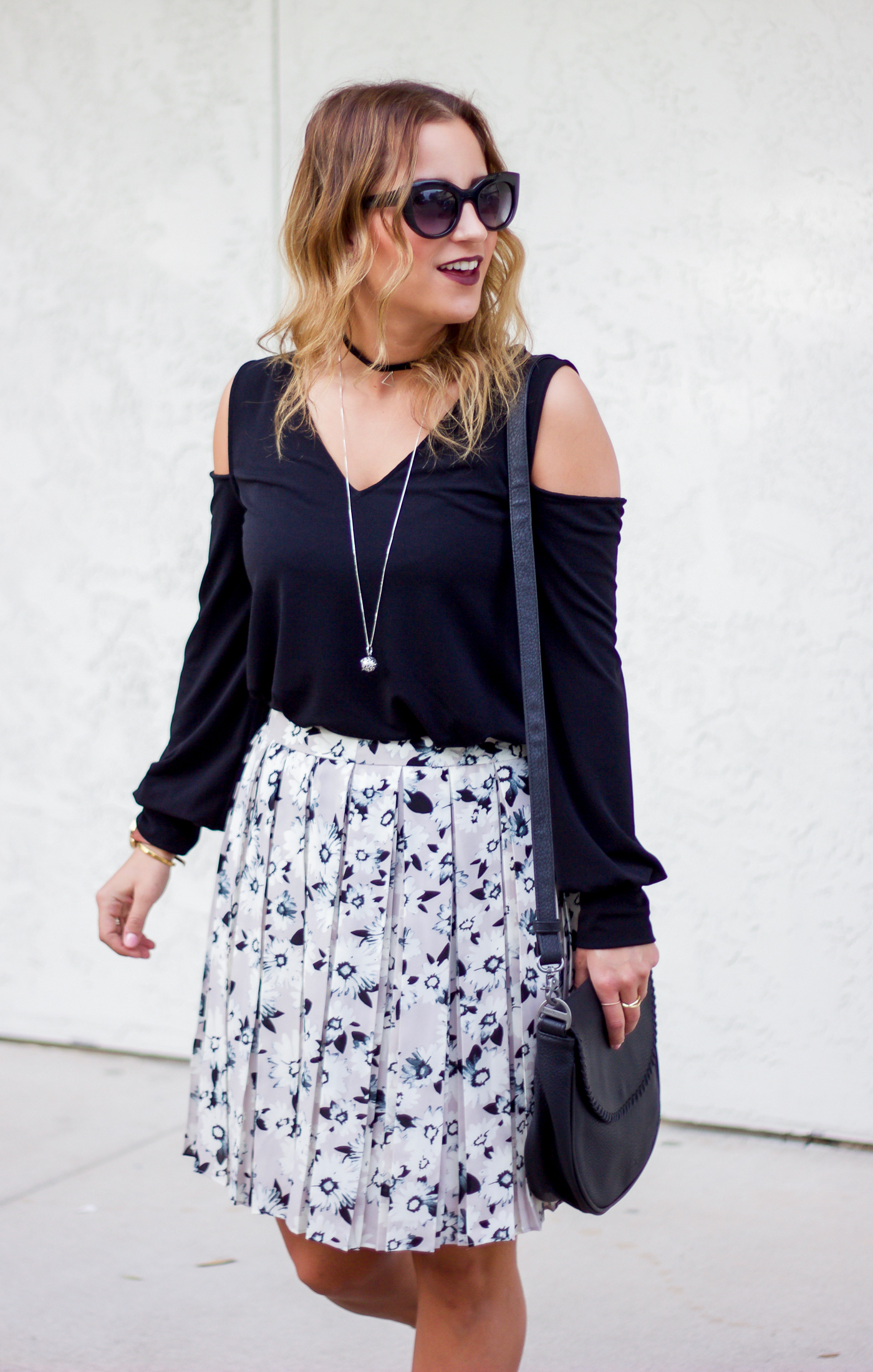 Jackie of Something About That is a fashion blogger, wearing a cold shoulder top from Express with a floral skirt from Banana Republic