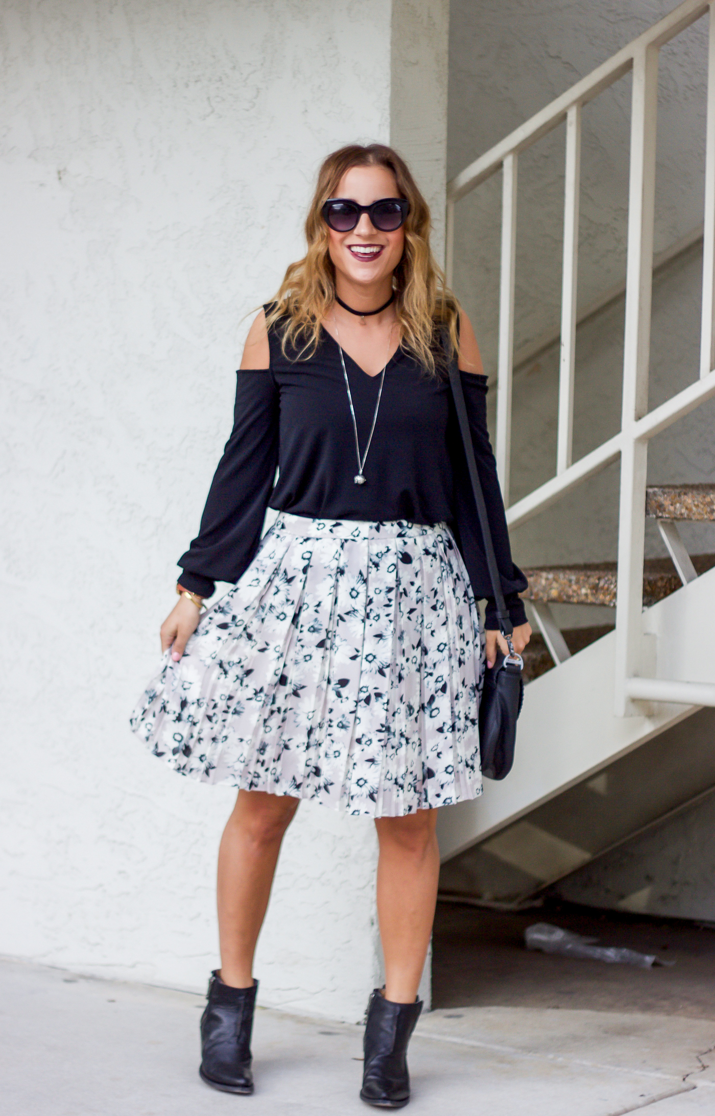 Toronto fashion and lifestyle blogger, Jackie Goldhar of Something About That, is wearing a cold shoulder top from Express and a floral box pleat skirt from Banana Republic