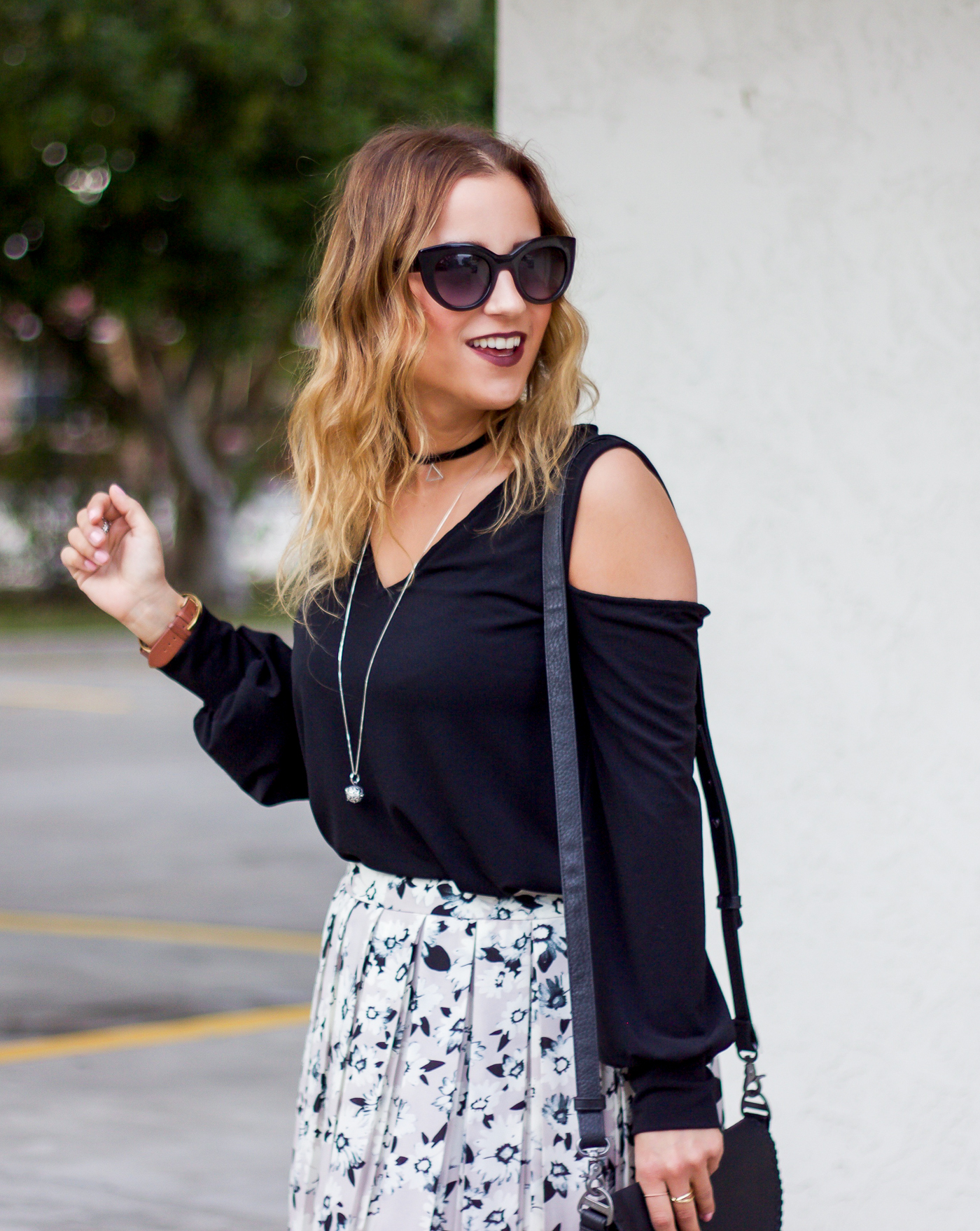 Jackie Goldhar is a Canadian fashion blogger, who's wearing a black v-neck cold shoulder tee from Express and Kate Spade sunglasses