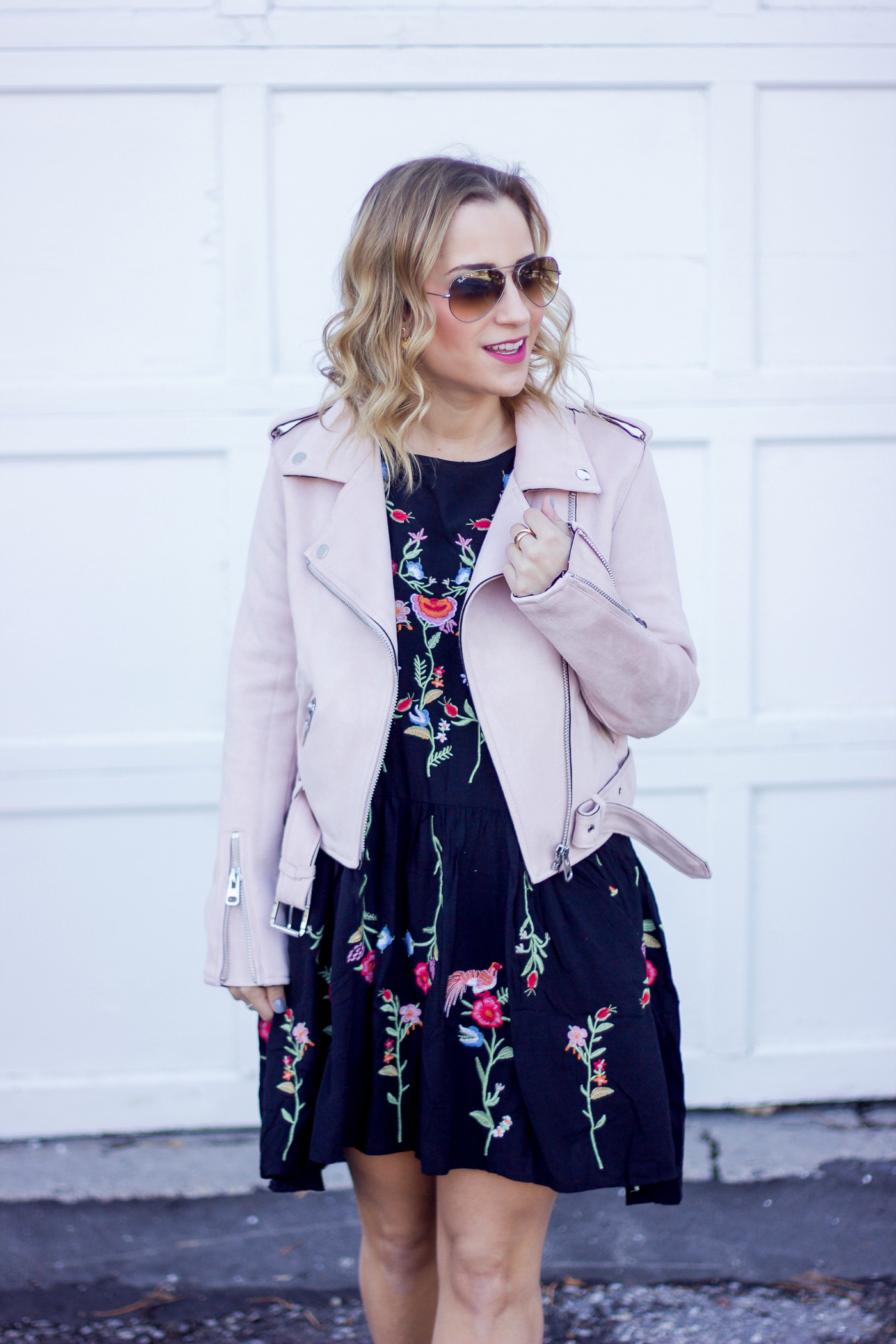 Toronto lifestyle and fashion blogger, Jackie of Something About That is wearing a pink moto jacket from Zara with an embroidered dress from Chicwish