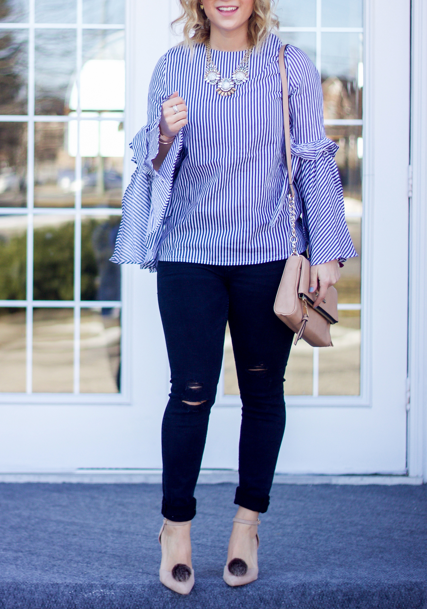 Canadian blogger is wearing a bell sleeve top with stripes from Chicwish with ripped black skinny jeans from Zara and pombons shoe accessories to spice up the look