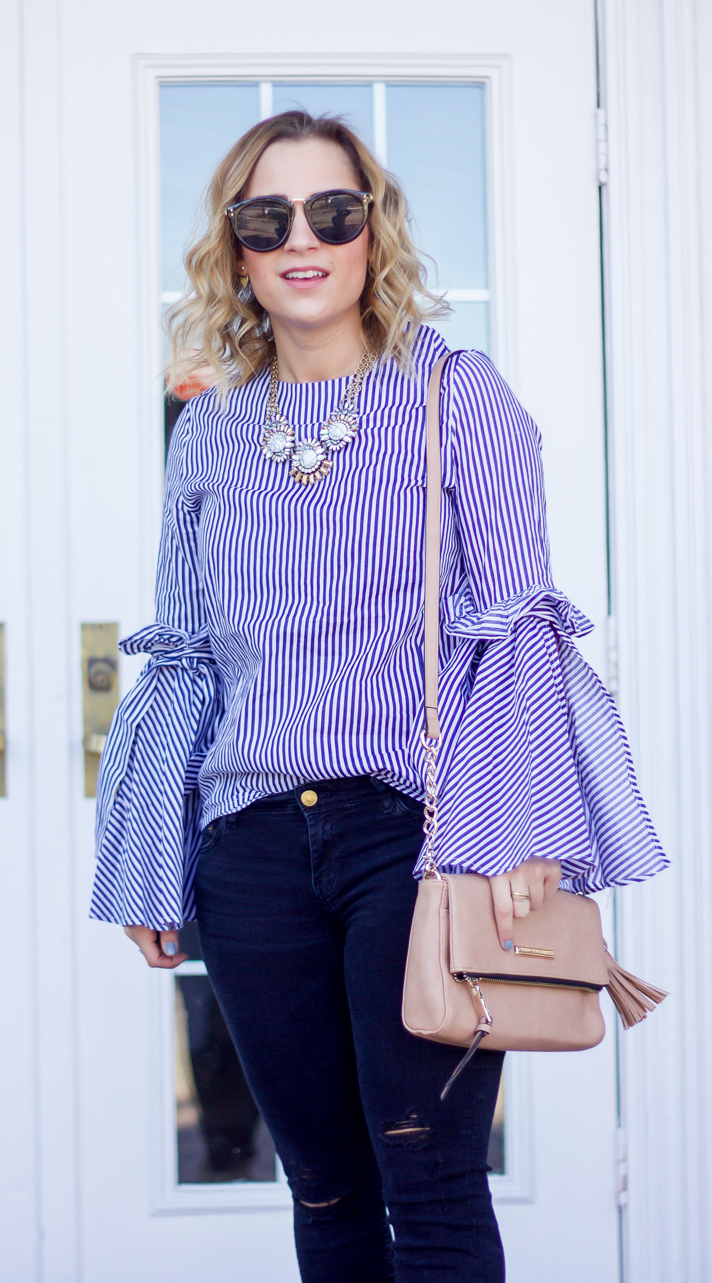 Canadian style blogger is wearing a striped top from Chicwish and a foldover bag from Poppy and Peonies