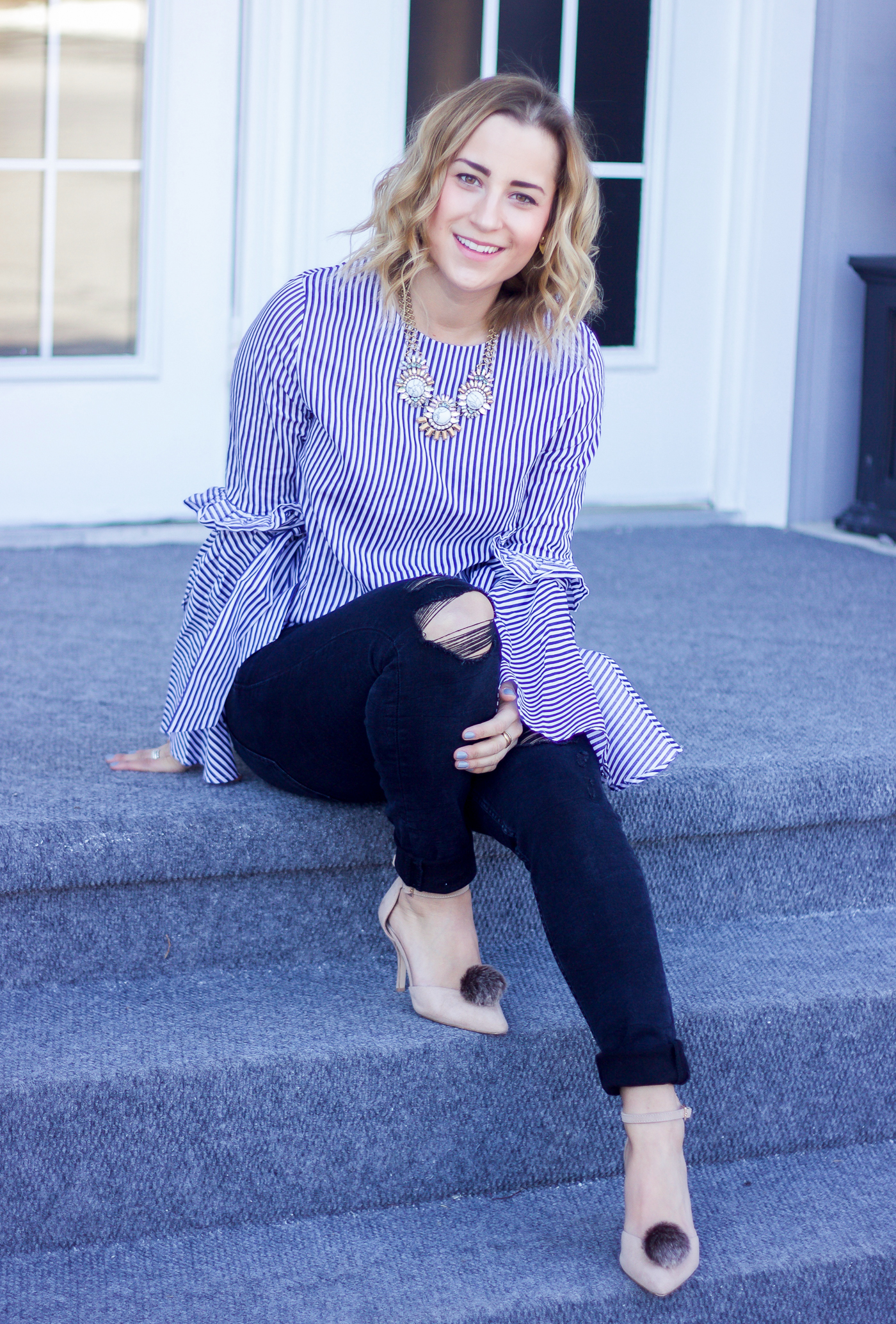 Jackie Goldhar is a Toronto-based lifestyle and fashion blogger, wearing a striped top from Chicwish and pumps with pombons to accessorize