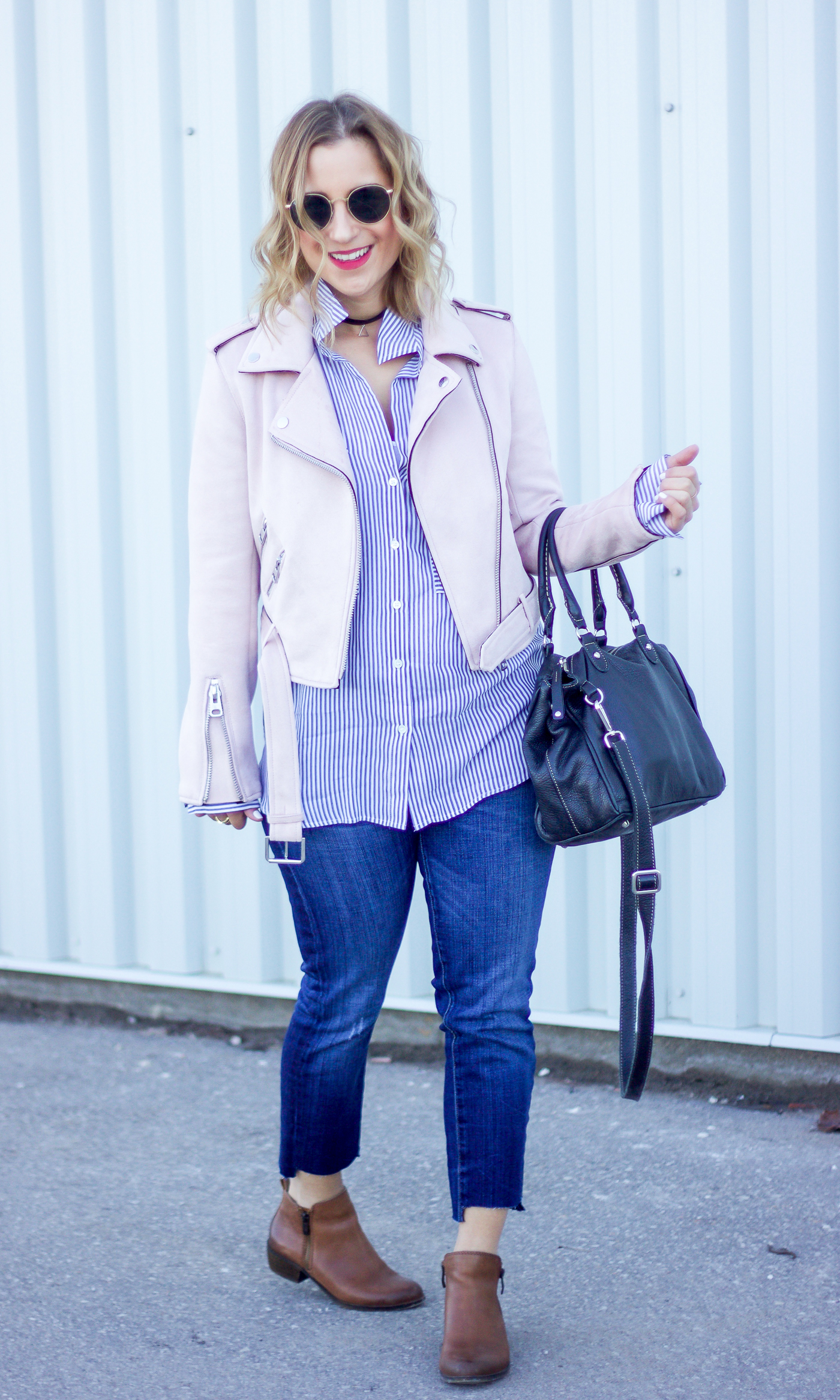 Canadian fashion blogger is wearing a pastel pink moto jacket from Zara with a striped button down blouse and jeans