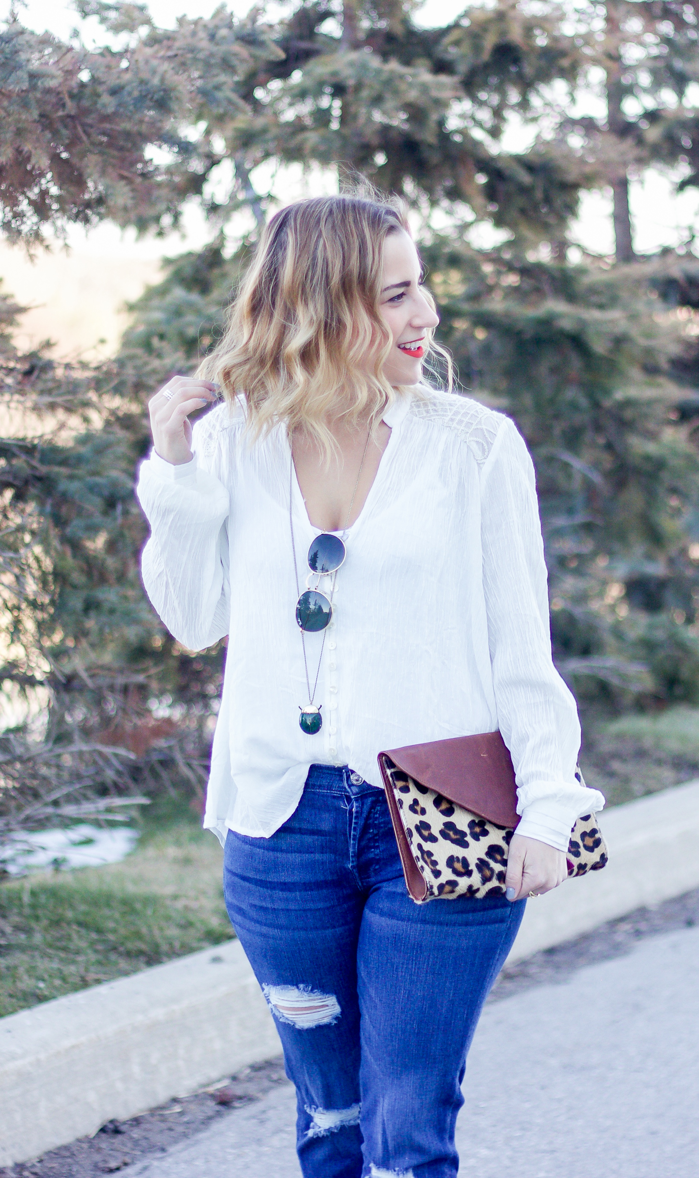Canadian fashion and lifestyle blogger, Jackie of Something About That, is wearing a white Free People boho blouse with distressed 7FAM boyfriend jeans
