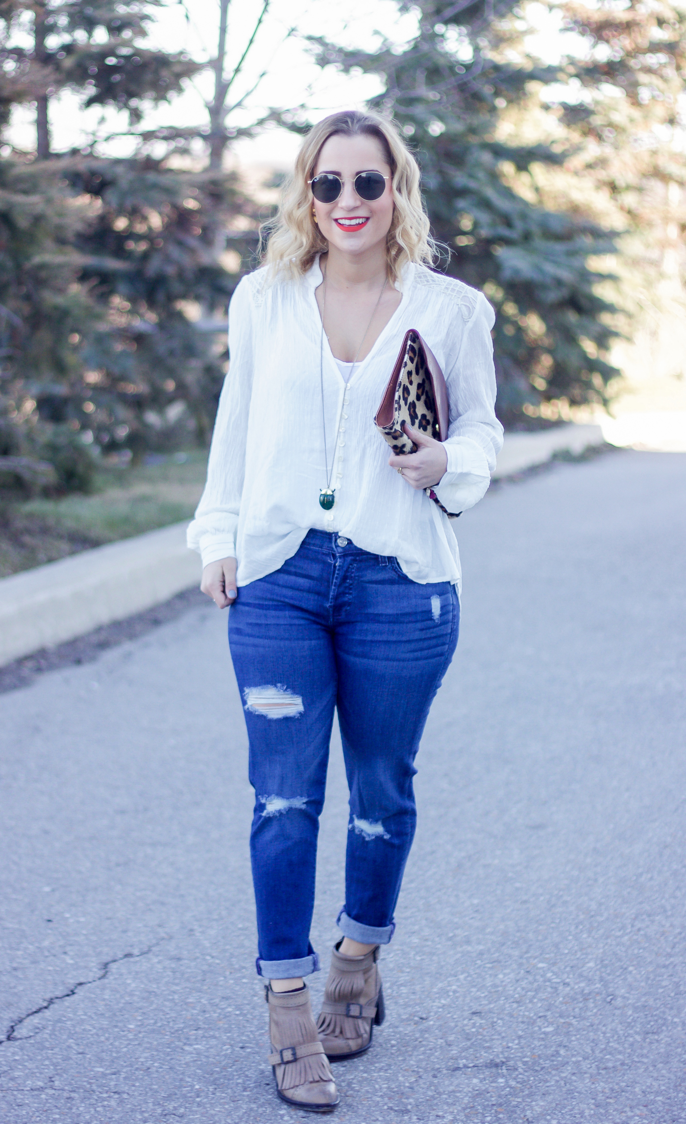 Jackie is a Canadian fashion and lifestyle blogger and she's wearing a white boho blouse from Free People, with ripped 7 For All Mankind boyfriend jeans and a BRAVE leather leopard clutch