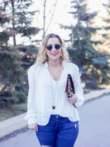 Jackie Goldhar is a Toronto-based fashion, beauty and lifestyle blogger and she's wearing Ray-ban round sunglasses with a white boho blouse from Free People