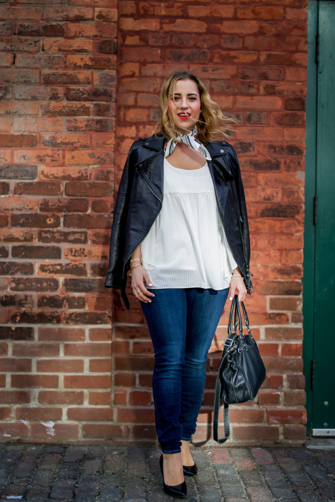 Canadian fashion and lifestyle blogger, Jackie of Something About That, wearing an edgy outfit, with her black leather moto jacket, white flowy top from Target and Fidelity skinny jeans