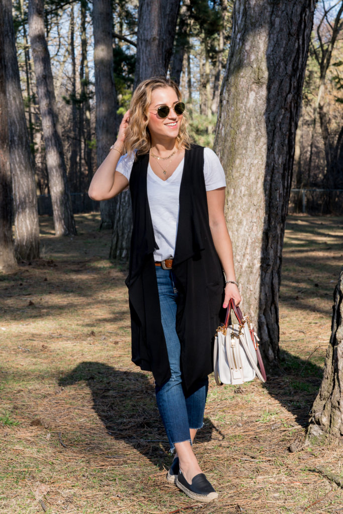 Canadian fashion and lifestyle blogger is wearing a black vest from Luved Clothing with a white Madewell v-neck t-shirt and cropped skinny jeans with her Coach Rogue bag