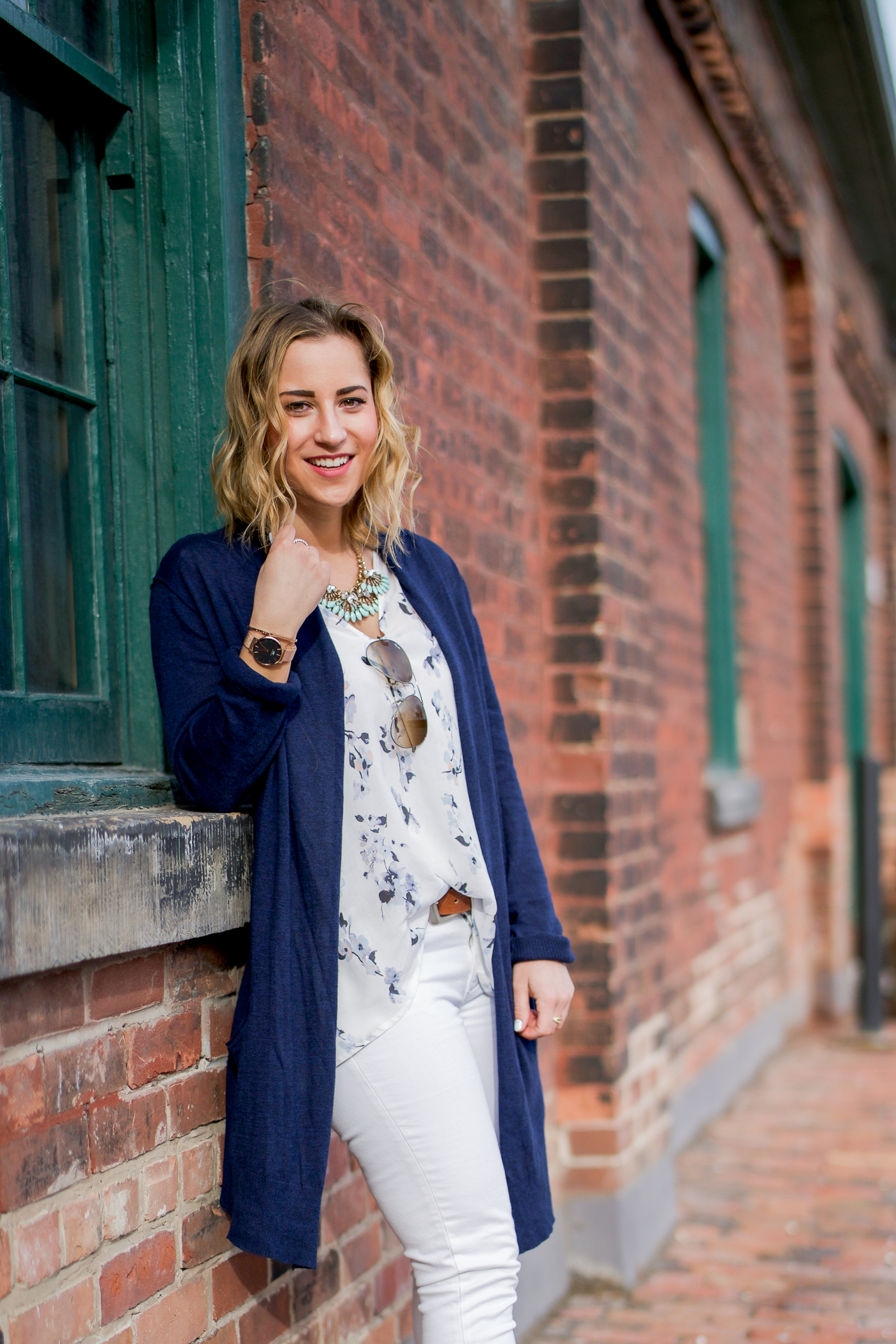 Toronto fashion and lifestyle blogger, Jackie of Something About That, wearing a spring outfit with white jeans from Gap, a floral top from Gentle Fawn and a navy cardigan from Joe Fresh
