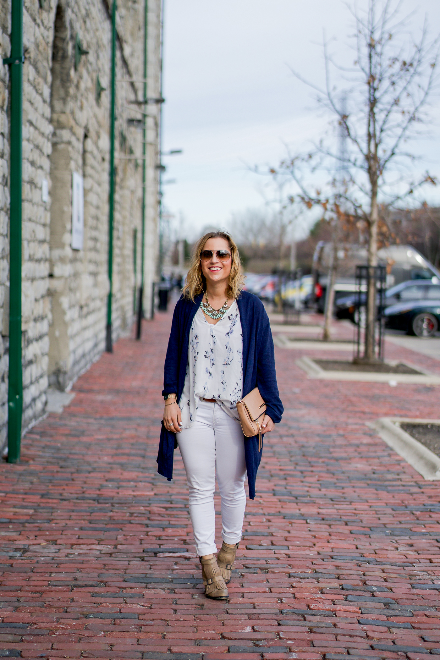 Canadian fashion blogger, Jackie of Something About That, wearing a spring outfit with white jeans and a white floral top from Gentle Fawn