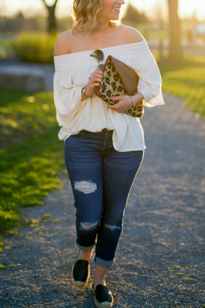 Jackie is a lifestyle and fashion blogger from Toronto and she's wearing an off the shoulder top from BB Dakota with a leopard clutch from Brave leather and ripped boyfriend jeans