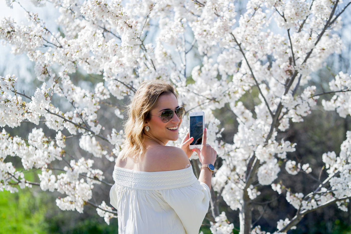 Canadian fashion and lifestyle blogger taking photos of the cherry blossoms at Centennial Park in Etobicoke