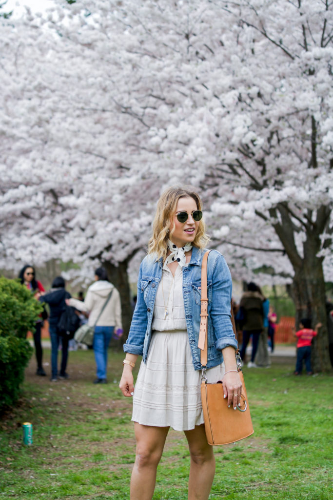 An easy chic and casual outfit is to wear a light denim jacket with a sundress, and accessorize with a neck scarf, as Canadian fashion blogger Jackie Goldhar did here
