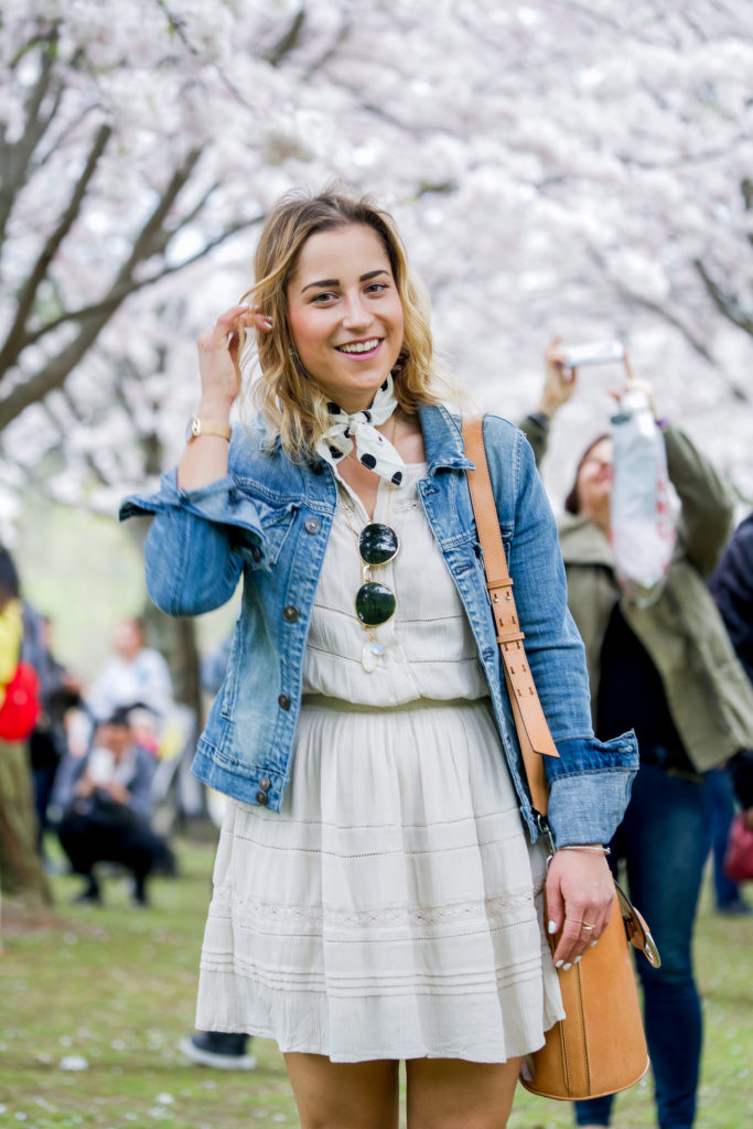 A chic, casual outfit idea for spring and summer is to wear a sundress with a light wash denim jacket and accessorize with a neck scarf and shoulder bag