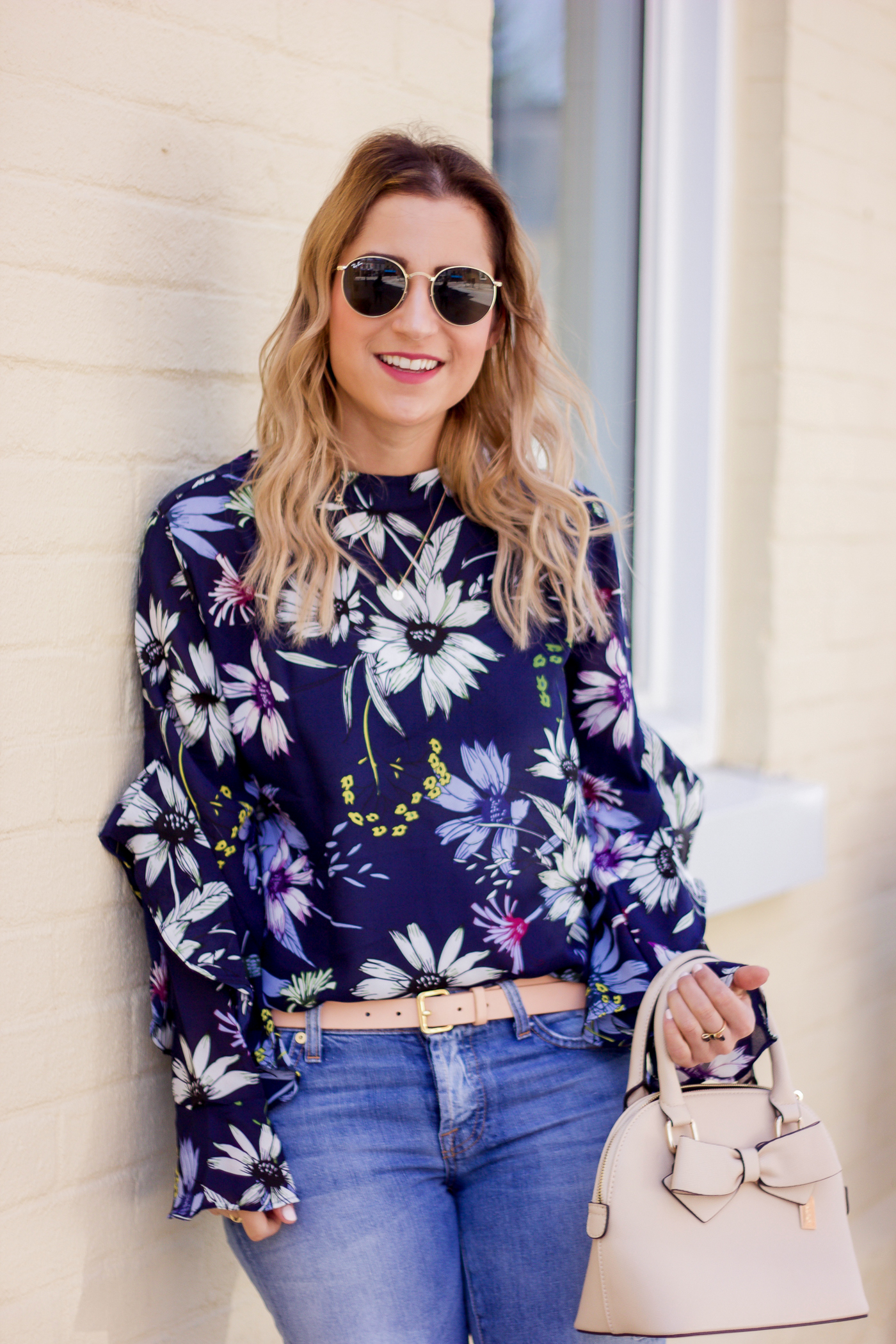 Cute spring outfit idea from a fashion blogger, with a navy floral blouse and light boyfriend jeans