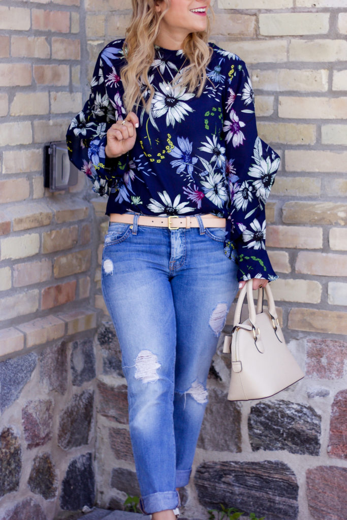 Canadian lifestyle and fashion blogger is wearing an easy, chic spring outfit idea, featuring a navy floral print blouse with light distressed boyfriend jeans