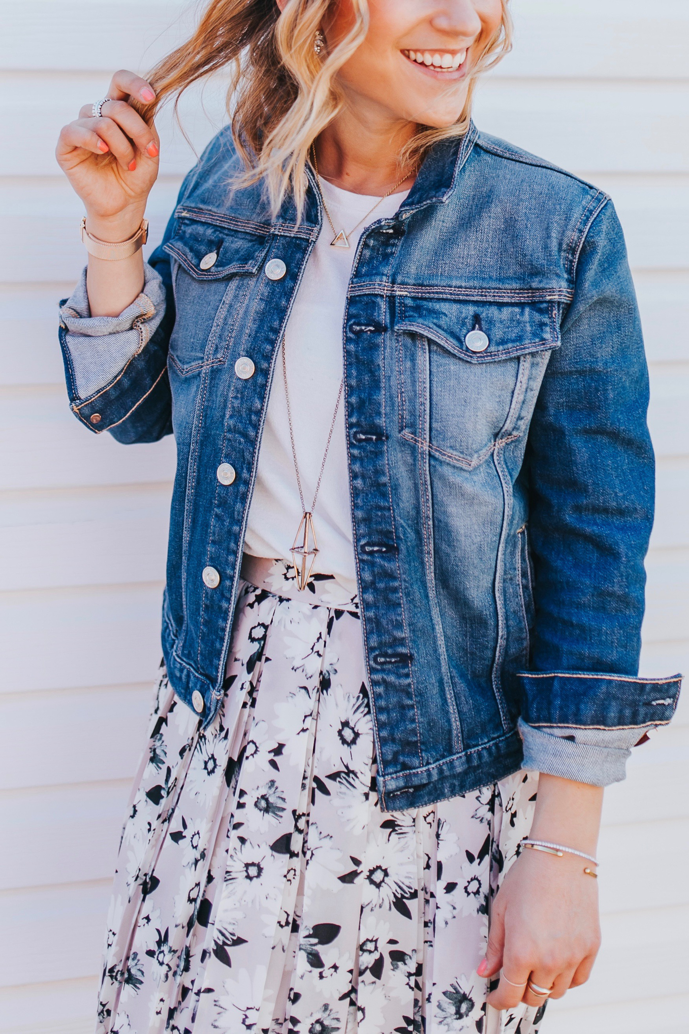 Canadian lifestyle and fashion blogger, Jackie of Something About That, wearing a 7FAM denim jacket with a pretty floral print skirt from Banana Republic