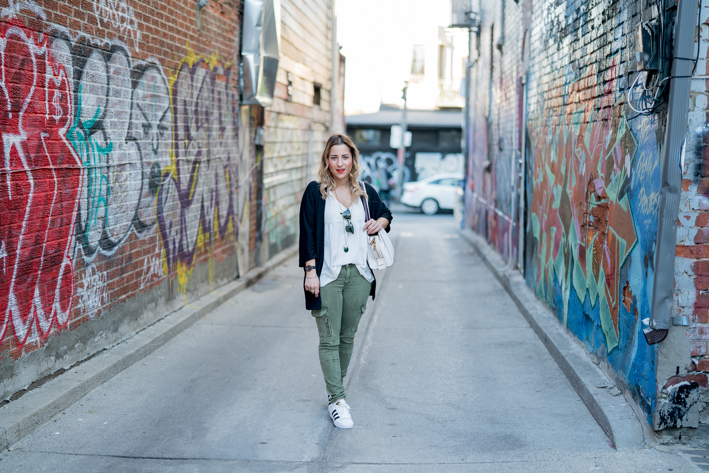 Exploring the Kensington Market district of Toronto in a black cardigan from Aritzia, White blouse from Target and skinny cargo pants from Zara