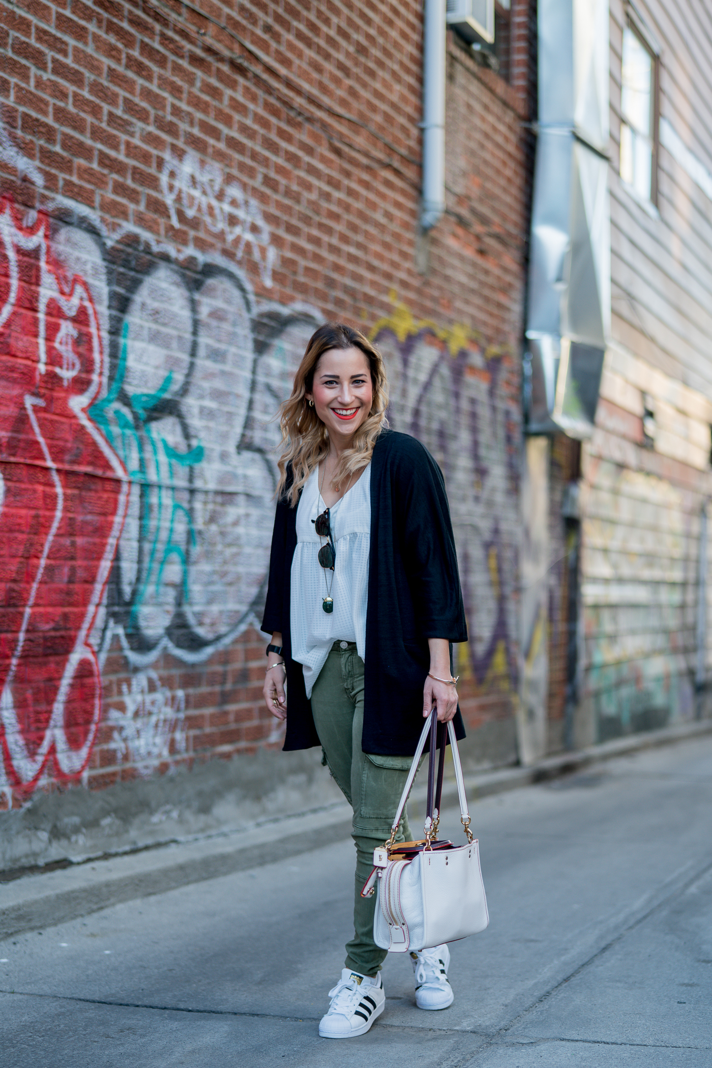 Jackie Goldhar is a Toronto-based lifestyle blogger, wearing a black Zlara cardigan from Aritzia with skinny cargo pants from Zara and Adidas Superstar sneakers
