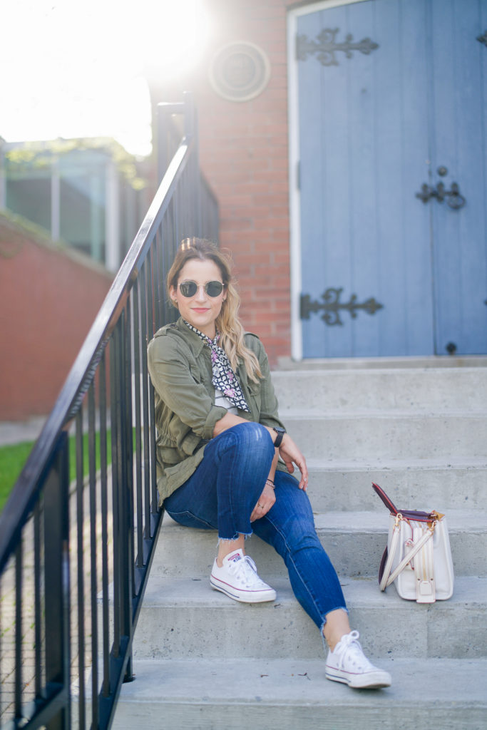 If you're looking for an effortless weekend outfit idea, try pairing a cargo jacket with jeans and Chucks, like Canadian fashion blogger, Jackie Goldhar did here