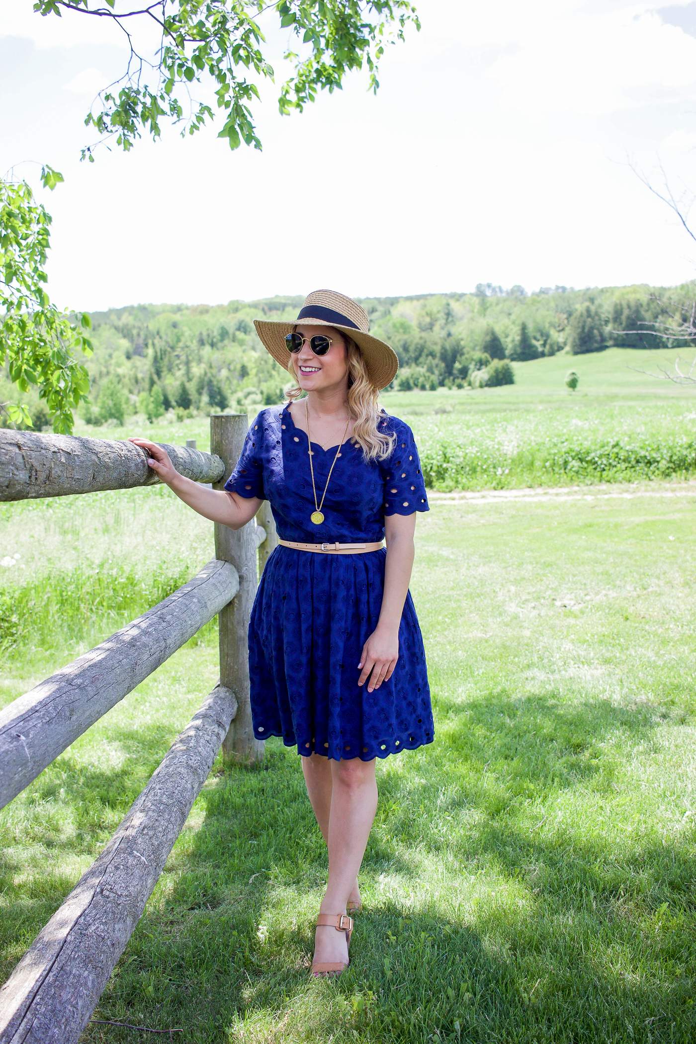 Toronto lifestyle blogger, Jackie of Something About That, is wearing a navy lace dress and a straw hat from H&M
