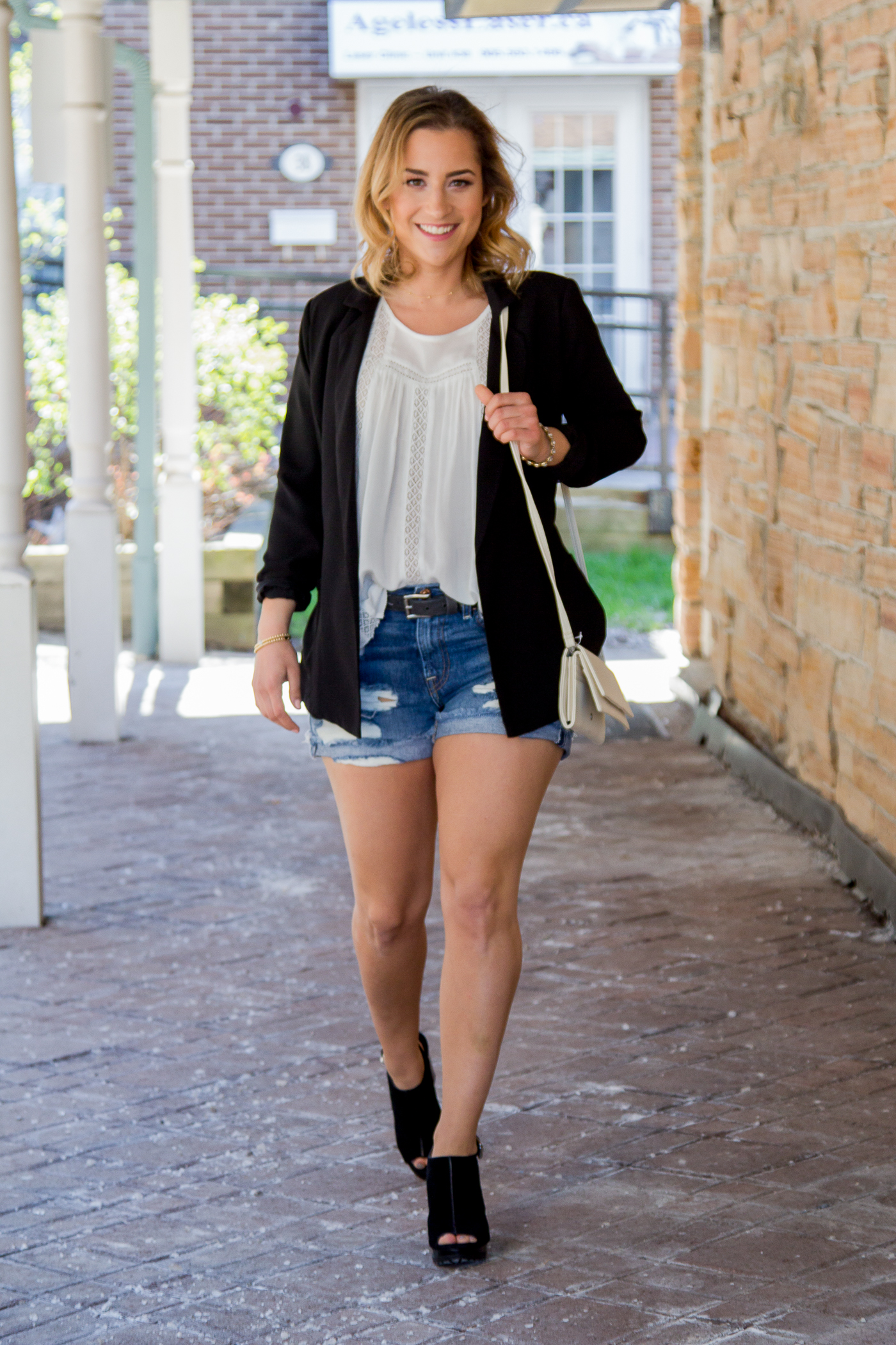 Toronto lifestyle and fashion blogger, Jackie of Something About That, wearing a chic summer outfit, featuring ripped denim shorts, a black blazer and flowy white Gentle Fawn top