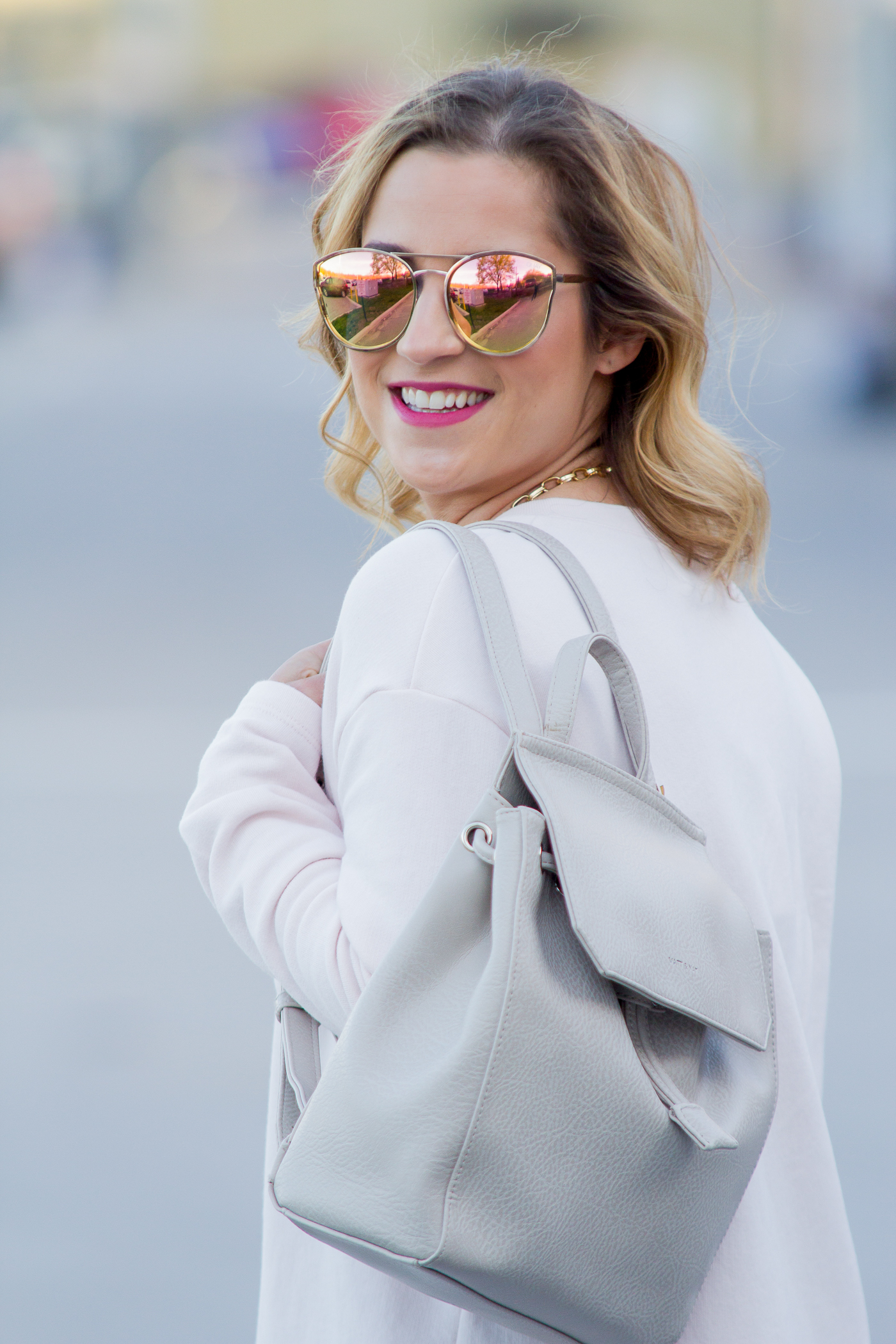 Jackie Goldhar is a Toronto-based fashion blogger, and she's wearing a backpack with rose gold sunnies from Quay
