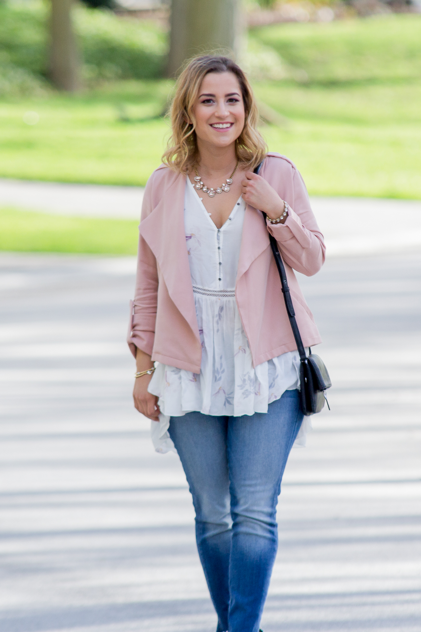 Casual summer outfit, with a pastel pink jacket, printed blouse and skinny jeans